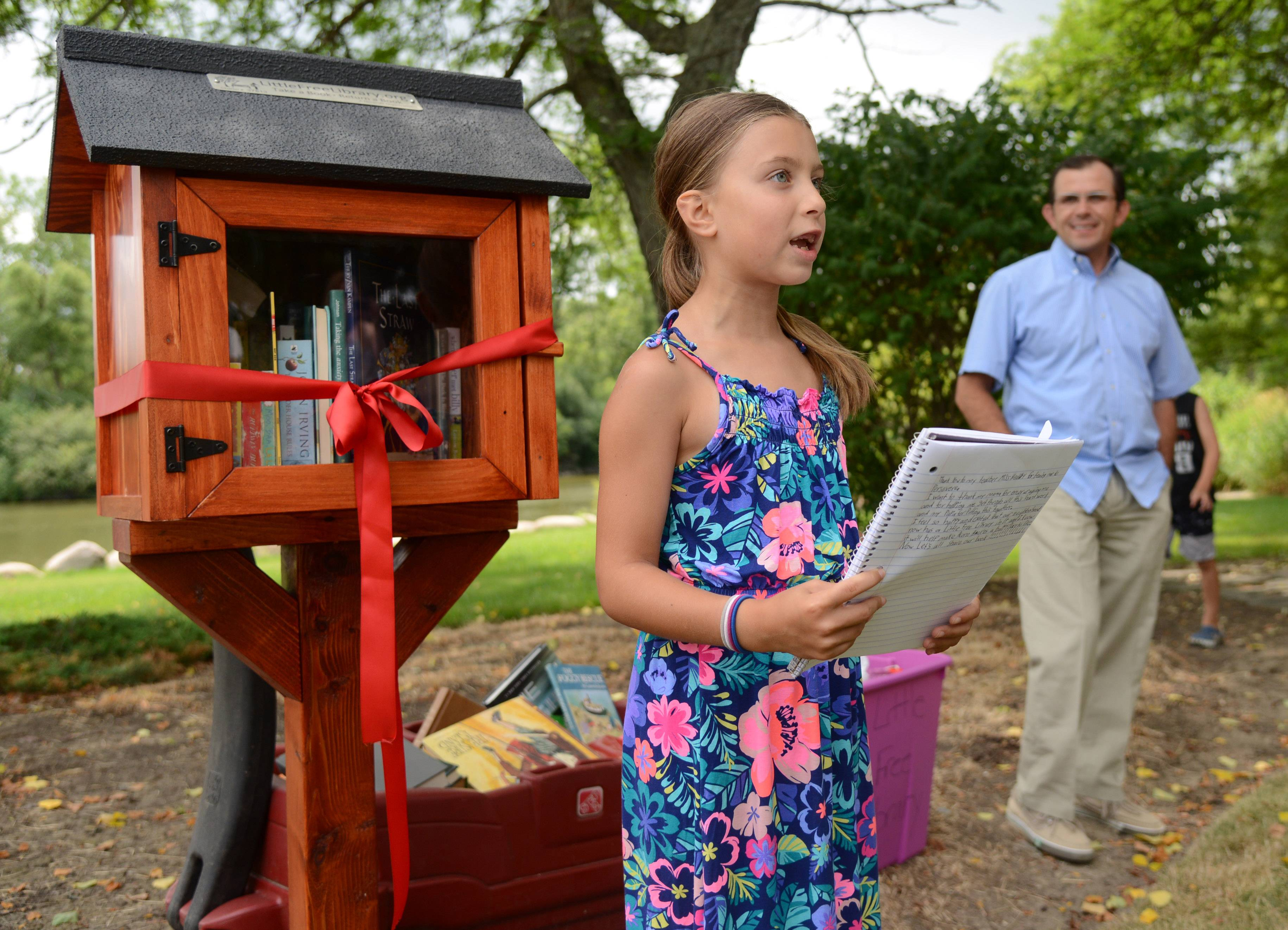 A Little Free Library opened Thursday in Hawthorn Woods thanks to the efforts of 7-year-old Maya Schultes. Maya talked about the project Thursday during an opening ceremony attended by Mayor Joseph Mancino, right, and other village leaders.