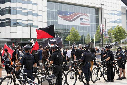 Protesters march as police look on near Public Square on Thursday, July 21, 2016, in Cleveland, during the final day of the Republican convention.