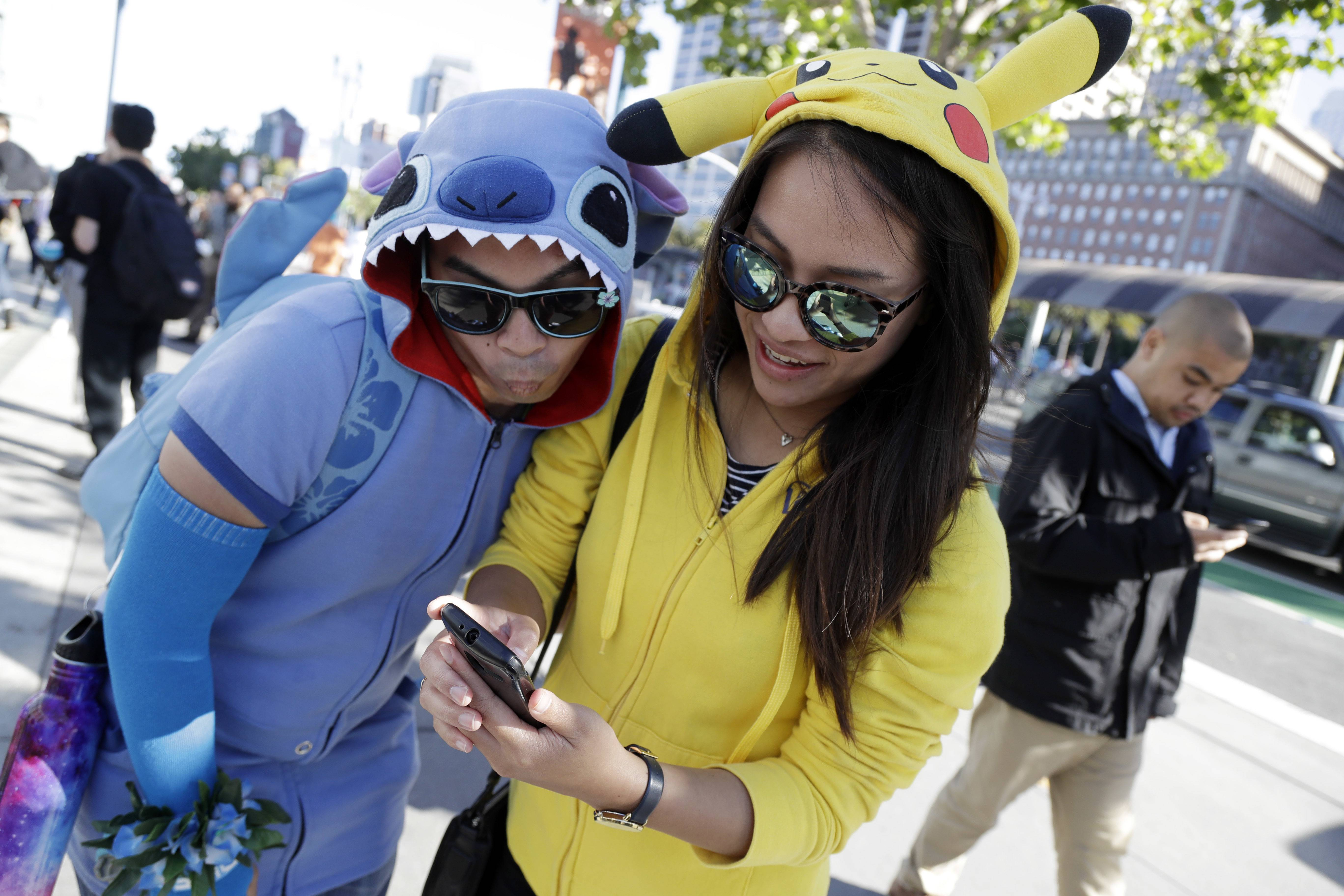 People costumed as the game's characters participate in a Pokemon Go search during a gathering of players Wednesday, July 20, 2016, in San Francisco.