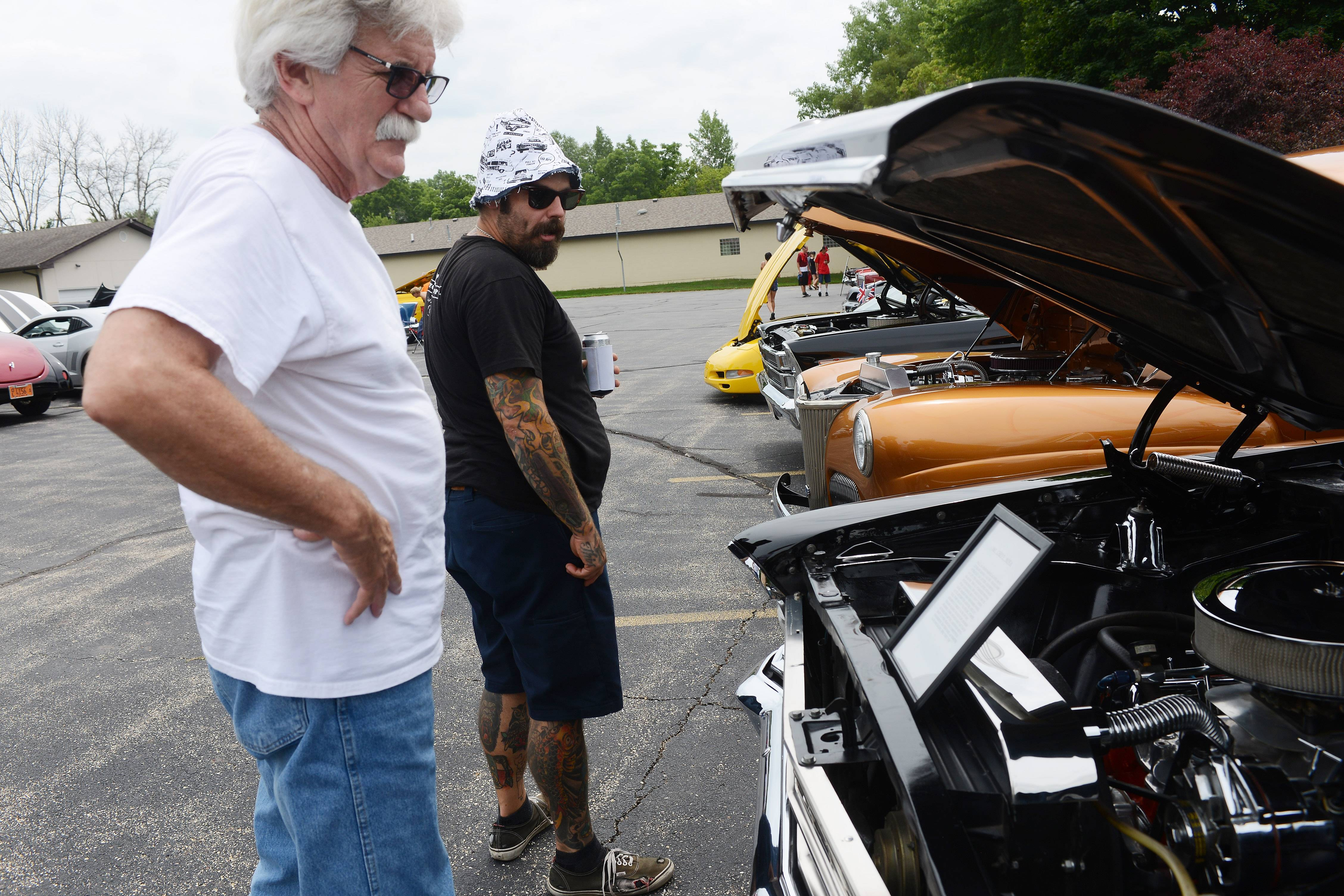 Donald Saville of Island Lake, left, and his son, Chad Saville of Hoffman Estates, view cars displayed during the Lakefest car show in Island Lake Saturday.
