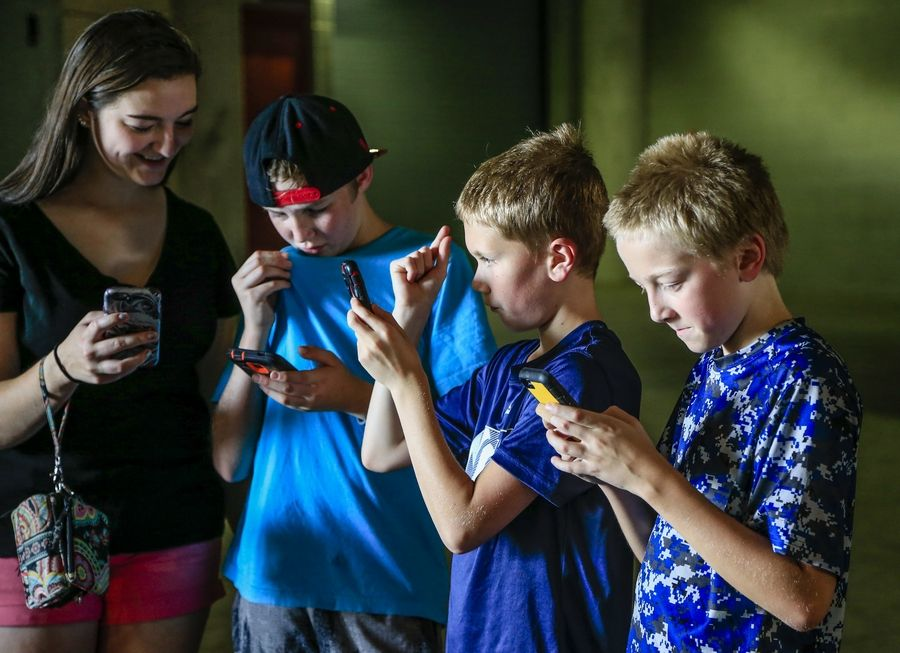 "Youngsters play during a ""Pokemon Go"" event at Memorial Stadium in Lincoln, Neb. One of the interesting debates over Pokemon Go, the addictive smartphone game that 9.5 million Americans play -- and probably a lot more than that now -- is whether it's truly augmented reality (AR), an up-and-coming companion technology to virtual reality (VR)."