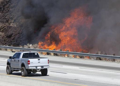 A wildfire flames from the Sand Fire near northbound Highway 14 near Shadow Pines Boulevard in Canyon Country on Friday, July 22, 2016. A wildfire north of Los Angeles has now burned about 2.3 square miles of bone-dry hillside. The fire erupted shortly after 2 p.m. Friday next to State Route 14 in Santa Clarita. The freeway is partially closed along with a section of Metrolink train track. About 200 firefighters and a half-dozen aircraft are battling the flames in 106-degree heat. (Katharine Lotze/The Santa Clarita Valley Signal via AP)