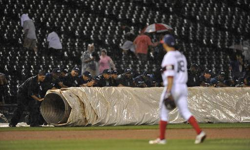 Members of the grounds crew unroll the tarp during a rain delay in the top of the ninth inning of a baseball game between the Chicago White Sox and Detroit Tigers on Saturday, July 23, 2016, in Chicago. (AP Photo/Paul Beaty)