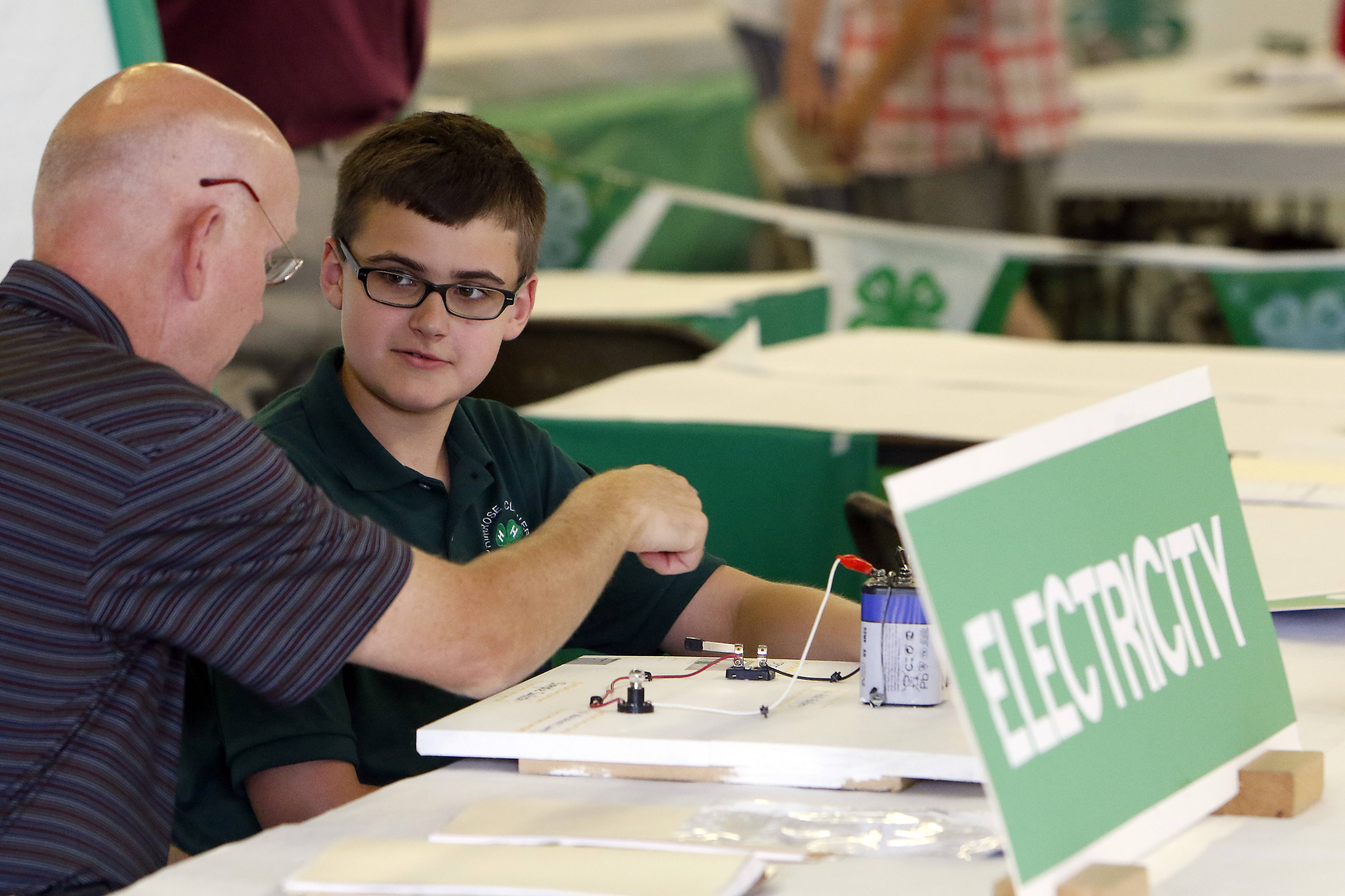 "Andrew McCafferty, 13, of Geneva, explains his electricity project to judge Ed Merkle of North Aurora. ""I really enjoy steering kids into the excitement of electricity,"" says Merkle, who is an electrical engineer and has been judging the Kane County Fair 4-H contest for 10 years."