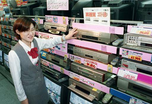 In this Oct. 31, 1998 photo, a salesclerk shows high quality VHS video casette recorders at a home and electrical appliance store in Osaka. Japanese electronics maker Funai Electric Co. says it's yanking the plug on the world's last video cassette recorder. A company spokesman, who requested anonymity citing company practice, confirmed Monday, July 25, 2016 that production will end sometime this month, although he would not give a date. (Kyodo News via AP) JAPAN OUT, MANDATORY CREDIT