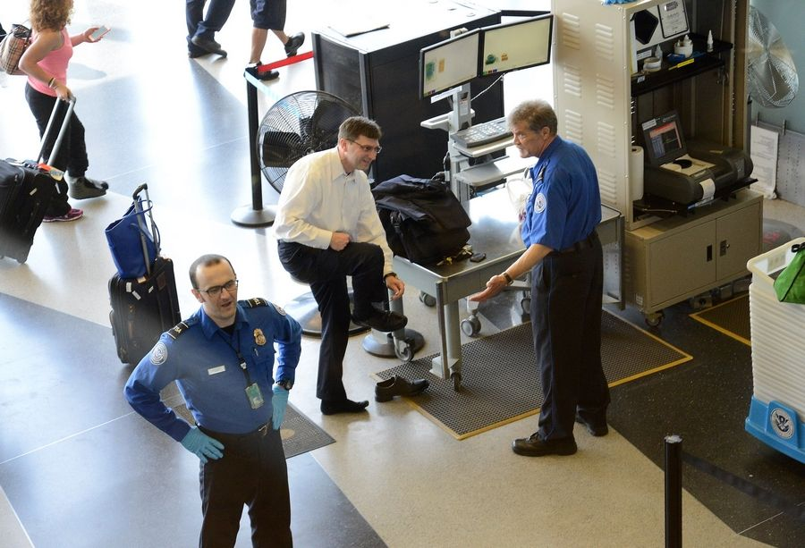 Passengers are inspected by TSA agents at Checkpoint 8 at O'Hare International Airport.