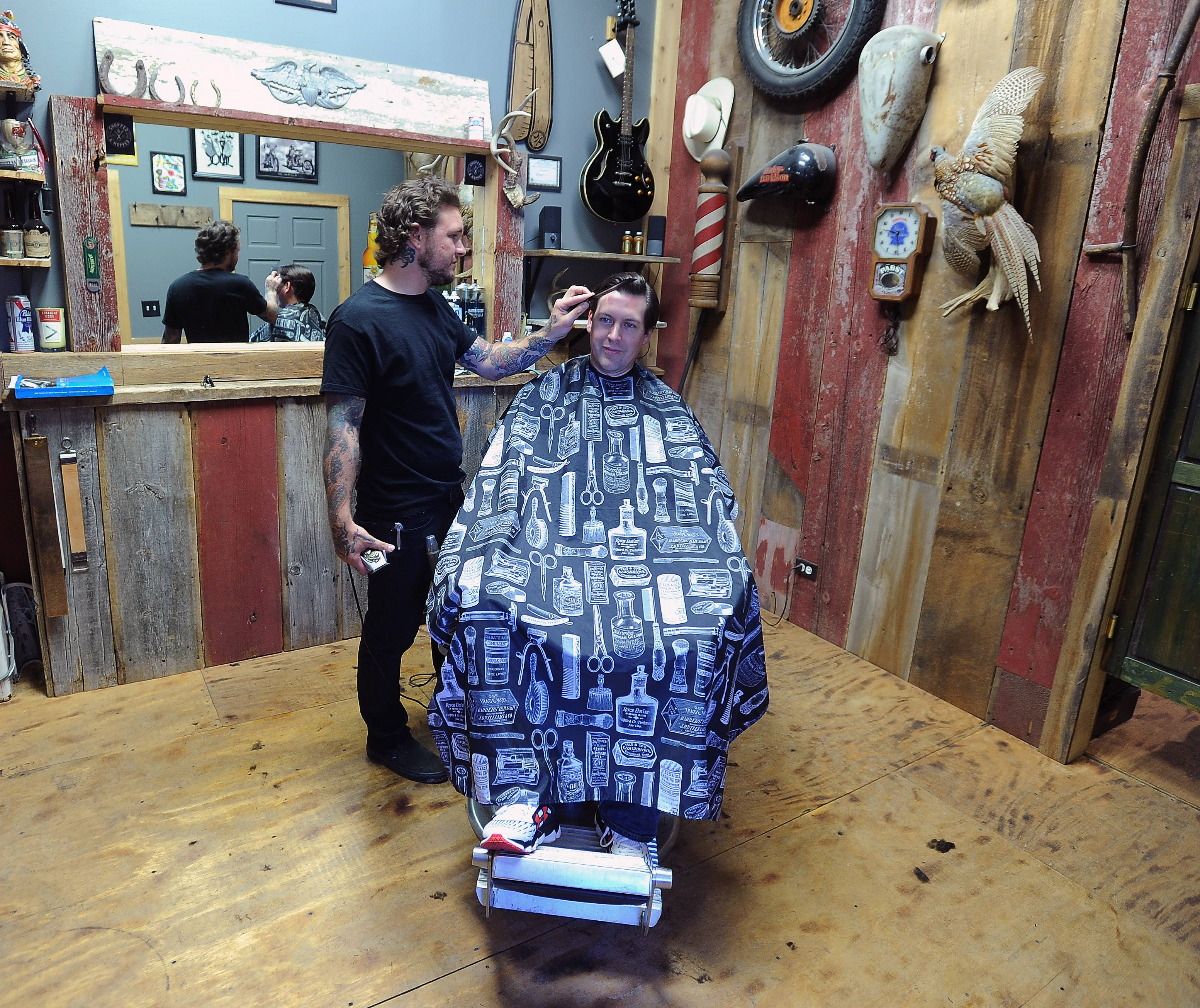 Barrington's Grassroots is more than a mere bar: Barber Tyler Rose gives Alan Weir of Lake Zurich a trim in the backroom.