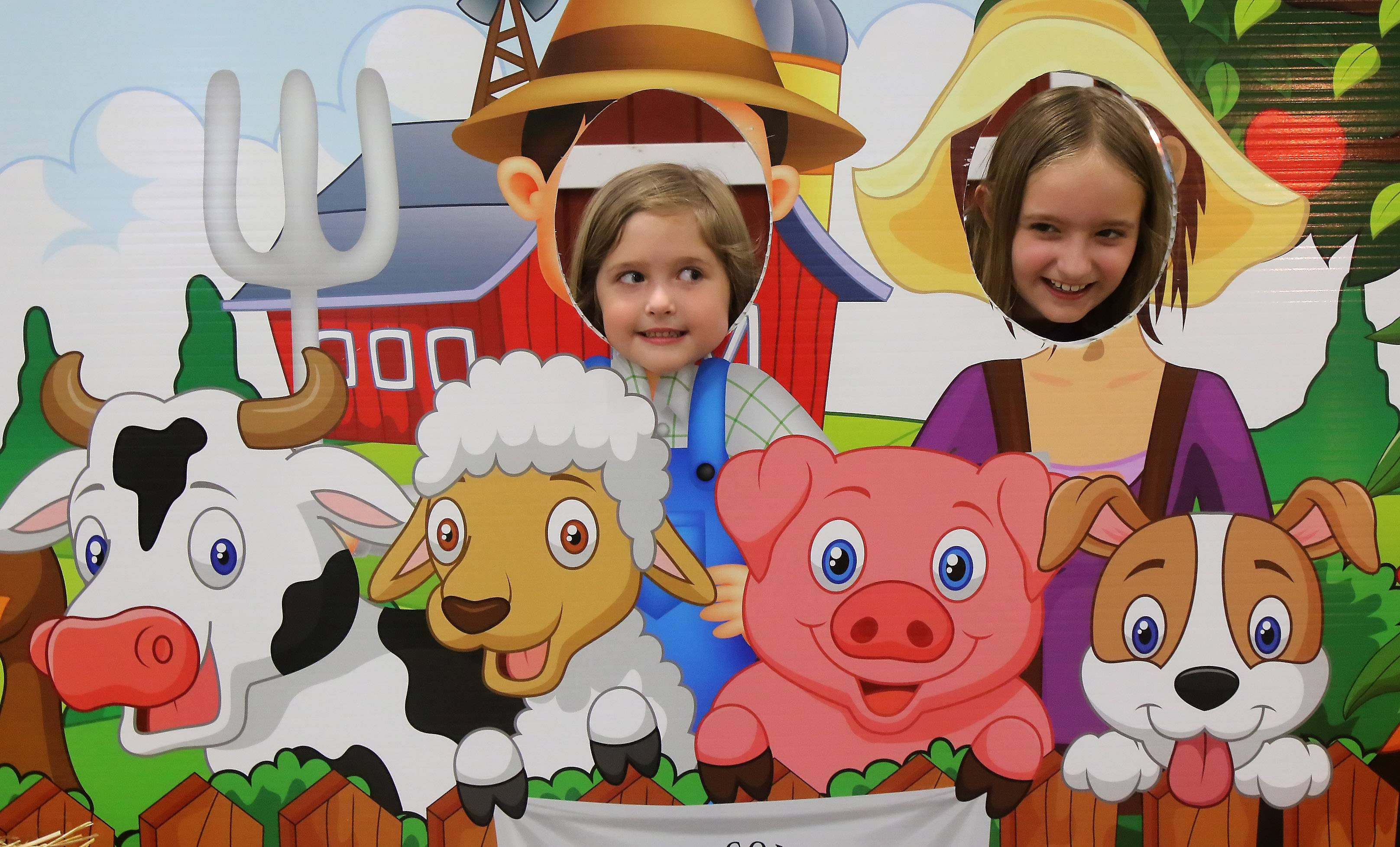 Clara Christner, 4, left, and Hailey Christner, 9, of Antioch pose for a picture with farm animals at the Ag Adventure! Wednesday during the Lake County Fair in Grayslake. The interactive miniature farm, hosted by the Lake County Farm Bureau, shows children how to milk a cow, ride a tractor and plant vegetables.