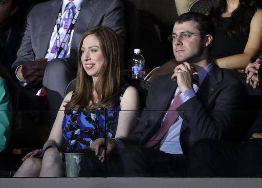 Chelsea Clinton, daughter of Democratic Presidential candidate Hillary Clinton, left, watches alongside her husband Marc Mezvinsky as her father speaks during the second day session of the Democratic National Convention in Philadelphia, Tuesday, July 26, 2016.