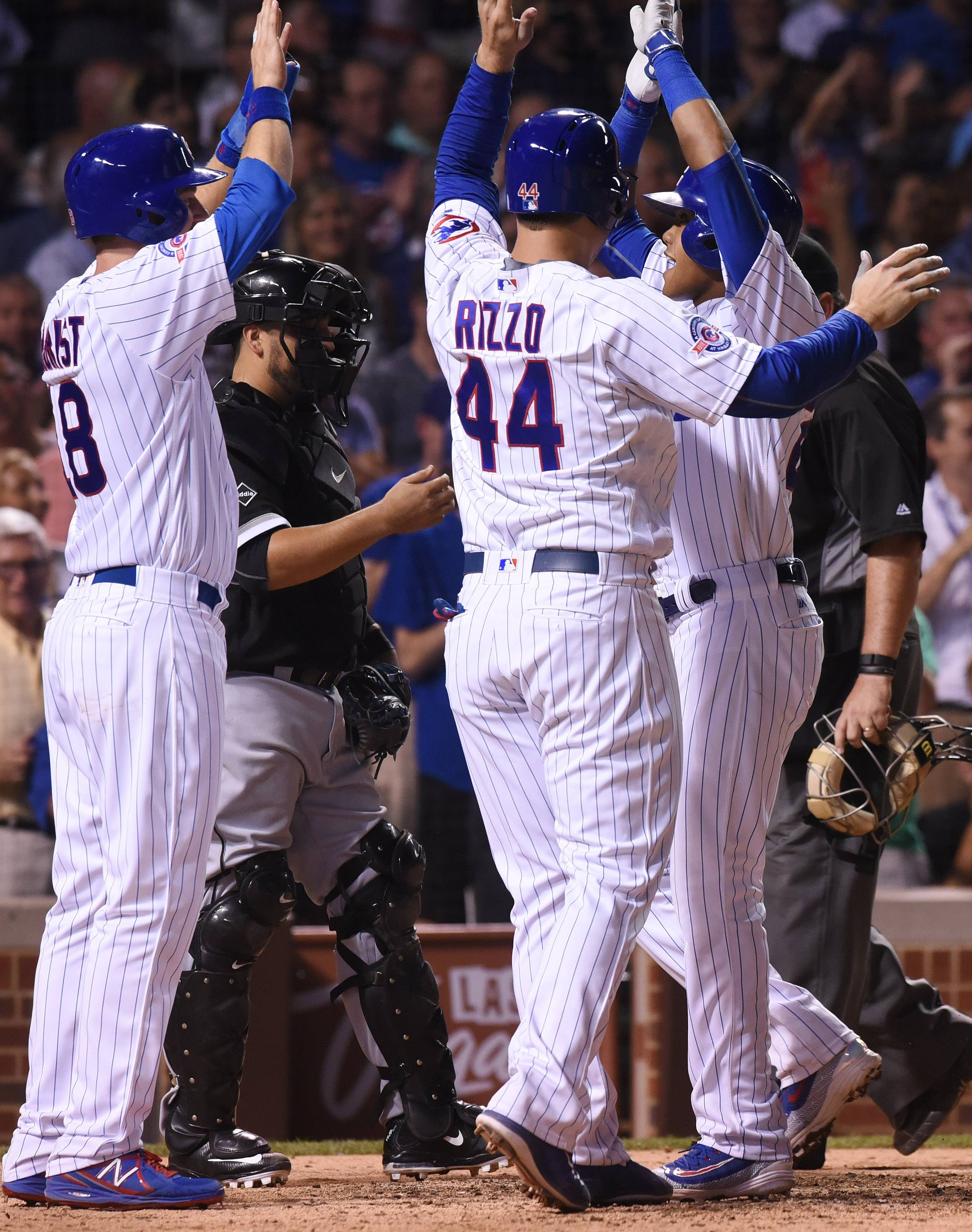 Addison Russell of the Chicago Cubs is greeted by teammates including anthony Rizzo, middle, and Ben Zobrist as he crosses the plate after hitting an eighth-inning grand slam during Wednesday's game against the White Sox at Wrigley Field in Chicago.