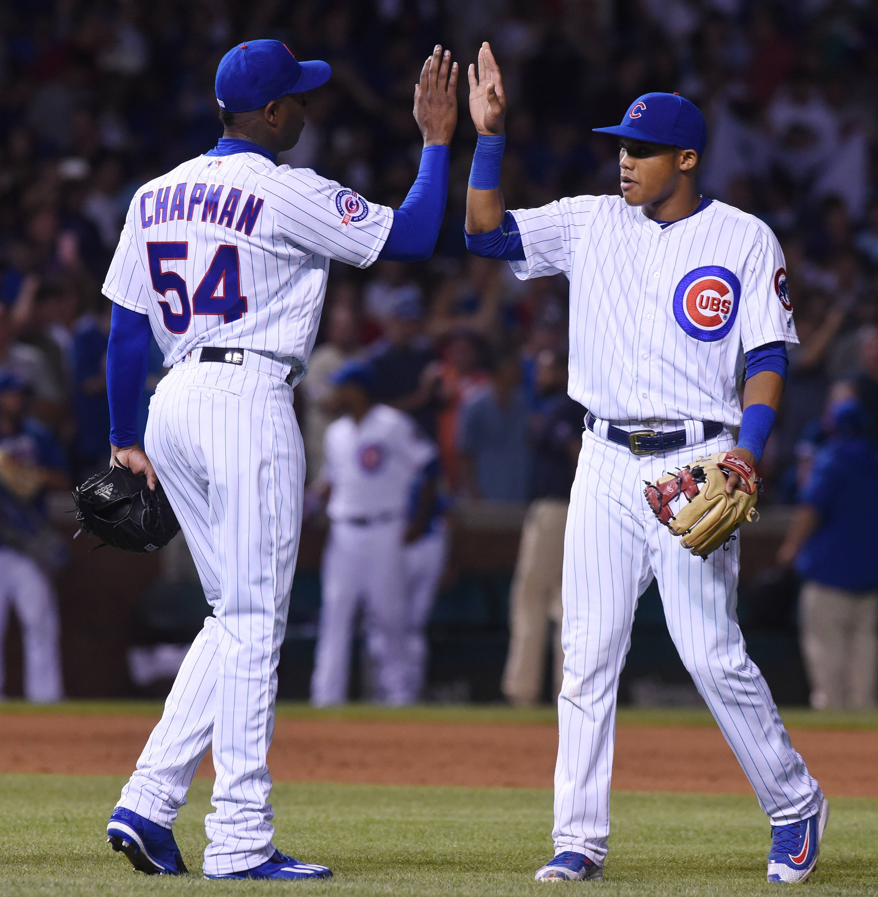 New Chicago Cubs relief pitcher Aroldis Chapman (54), left, high-fives shortstop Addison Russell following Wednesday's 8-1 victory over the White Sox at Wrigley Field in Chicago.
