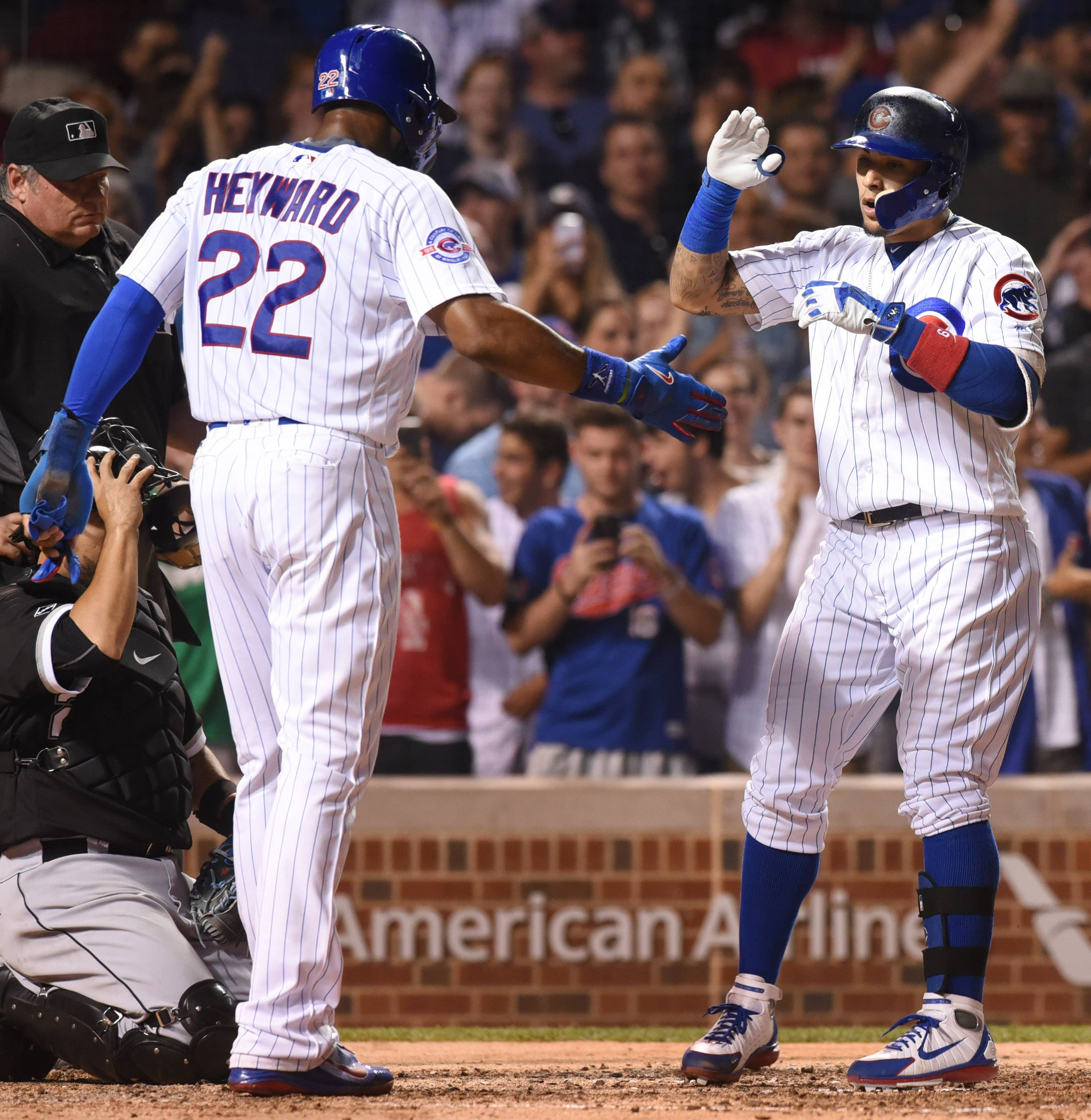 Joe Lewnard/jlewnard@dailyherald.comJavier Baez of the Cubs celebrates with teammate Jason Heyward as he crosses the plate after hitting a two-run home run to break a 1-1 tie during the bottom of the seventh inning of Wednesday's game against the White Sox at Wrigley Field in Chicago.