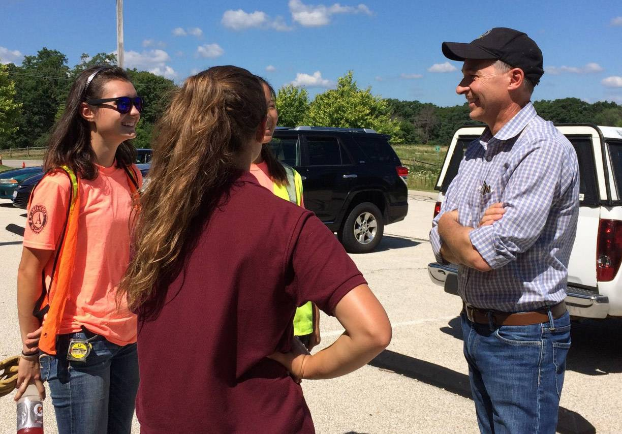 Lake County Forest Preserve Executive Director Ty Kovach, right, speaks with members of the Youth Conservation Corps, including crew leader Emily Schlebecker, left, at the Lakewood Forest Preserve on Tuesday.