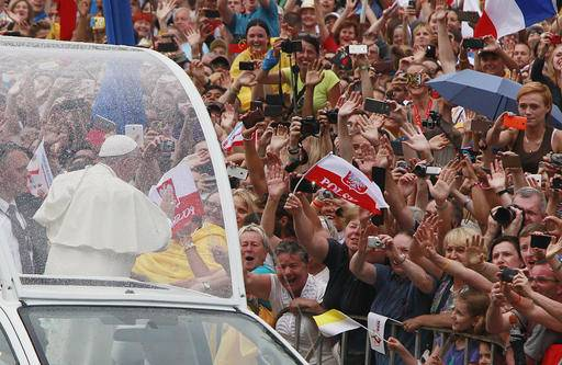 Pope Francis salutes faithful and pilgrims on his way to the royal Wawel Castle in Krakow, Poland, Wednesday, July 27, 2016. Pope Francis has been greeted in Poland by President Andrzej Duda and hundreds of singing and cheering people as he arrived at the airport in Krakow. (AP Photo/Czarek Sokolowski)