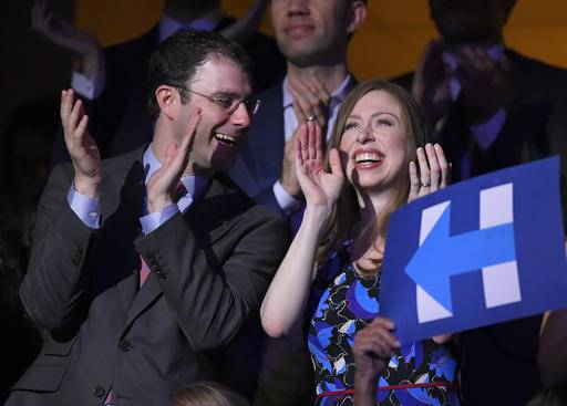 Chelsea Clinton, daughter of Democratic Presidential candidate Hillary Clinton and husband Marc Mezvinsky smile as Democratic Presidential candidate Hillary Clinton appears on screen live during the second day of the Democratic National Convention in Philadelphia , Tuesday, July 26, 2016.