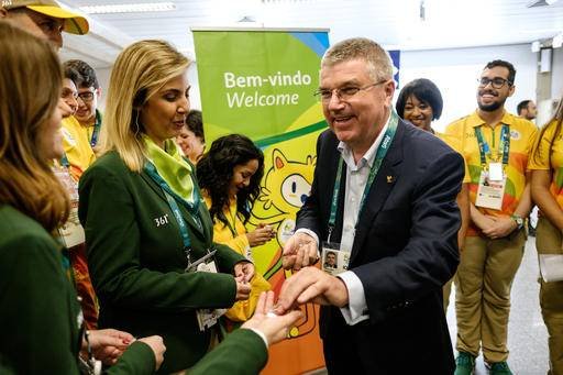 Tomas Bach, President of the International Olympic Committee, hands out an Olympic pin on his arrival for Rio 2016 Olympic games at Antonio Carlos Jobim Galeao International Airport in Rio de Janeiro, Brazil, July 27, 2016. (Yasuyochi Chiba/Pool Photo via AP)
