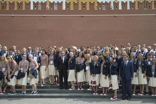 President of Russia's Olympic Committee Alexander Zhukov, fourth right, and Sports Minister Vitaly Mutko, center, pose for a photo with Russia's National Olympic team members outside the Kremlin wall, before a meeting with Russian President Vladimir Putin, in Moscow, Russia, Wednesday, July 27, 2016. At least 105 athletes from the 387-strong Russian Olympic team announced last week have been barred from the Rio Games in connection with the country's doping scandal. (AP Photo/Pavel Golovkin)