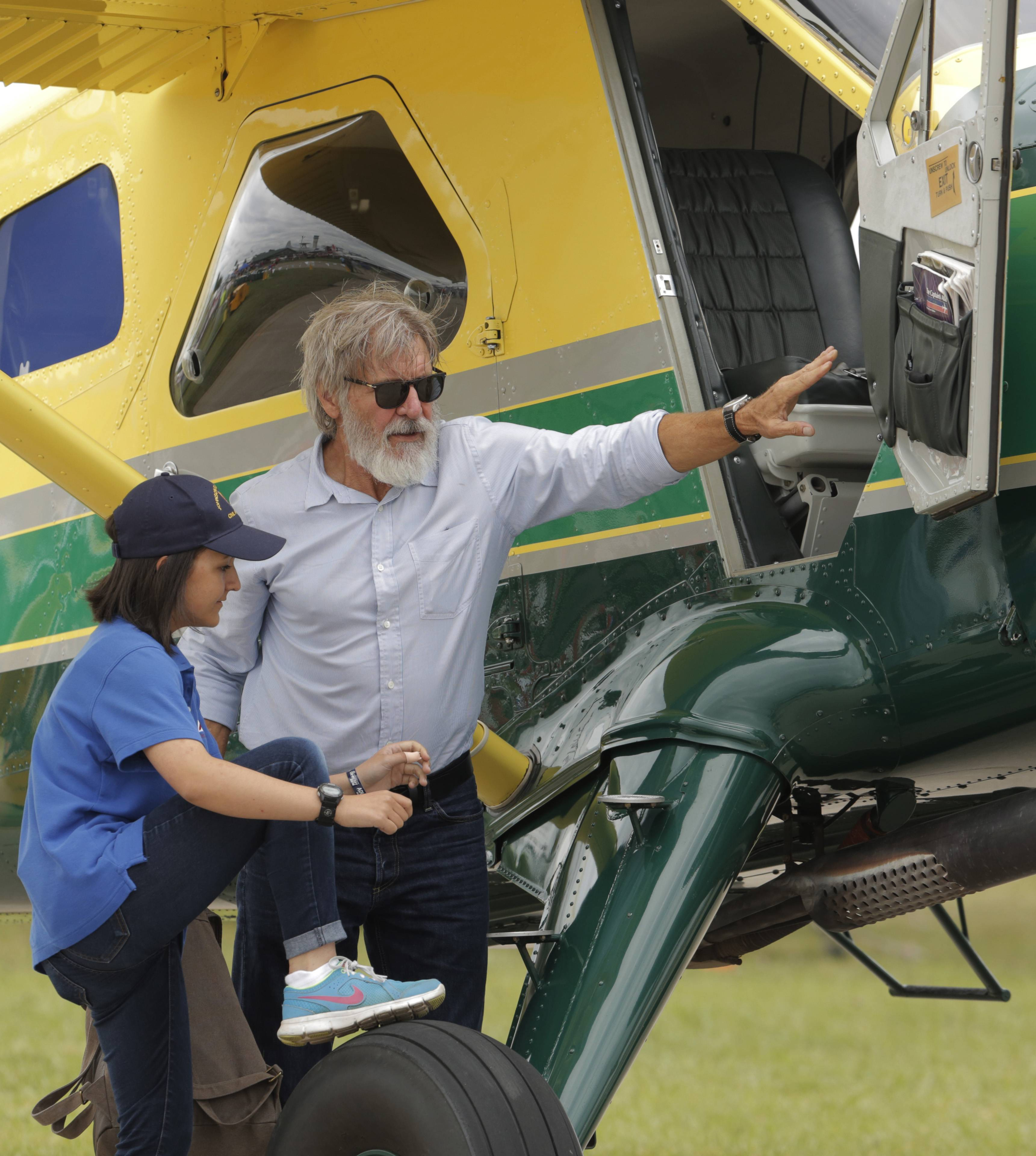 Harrison Ford opens the door on his plane for Jodie Gawthorp of Westchester, 16, who was selected to fly with Ford during the Experimental Aircraft Associations AirVenture air show over Wittman Regional Airport in Oshkosh, Wis., Thursday.