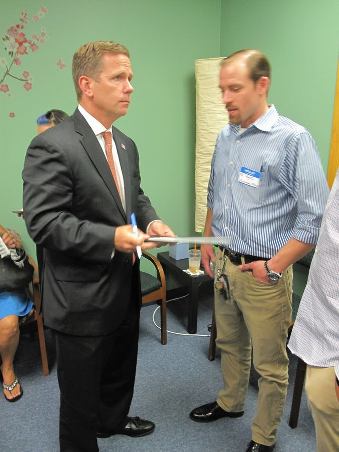 U.S. Rep. Bob Dold talks with Bill Ayars, a former heroin user and Barrington High School graduate who now works for Brightside treatment center in Northbrook.
