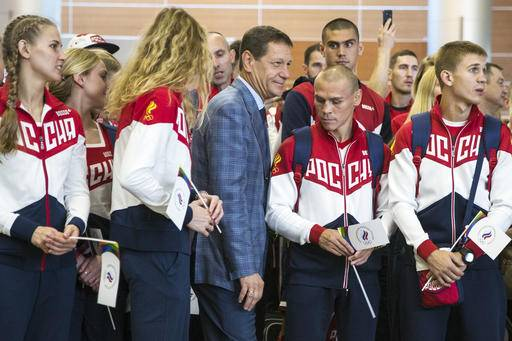Russian Olympic Committee President Alexander Zhukov, center, passes through Russia's National Olympic team members during the ceremony before Russian team's departure for Rio Olympics, in Moscow's Sheremetyevo, Russia, Thursday, July 28, 2016. More than 100 Russians from the 387-strong Olympic team have been banned so far from going to Rio de Janeiro over the country's doping scandal. (AP Photo/Pavel Golovkin)