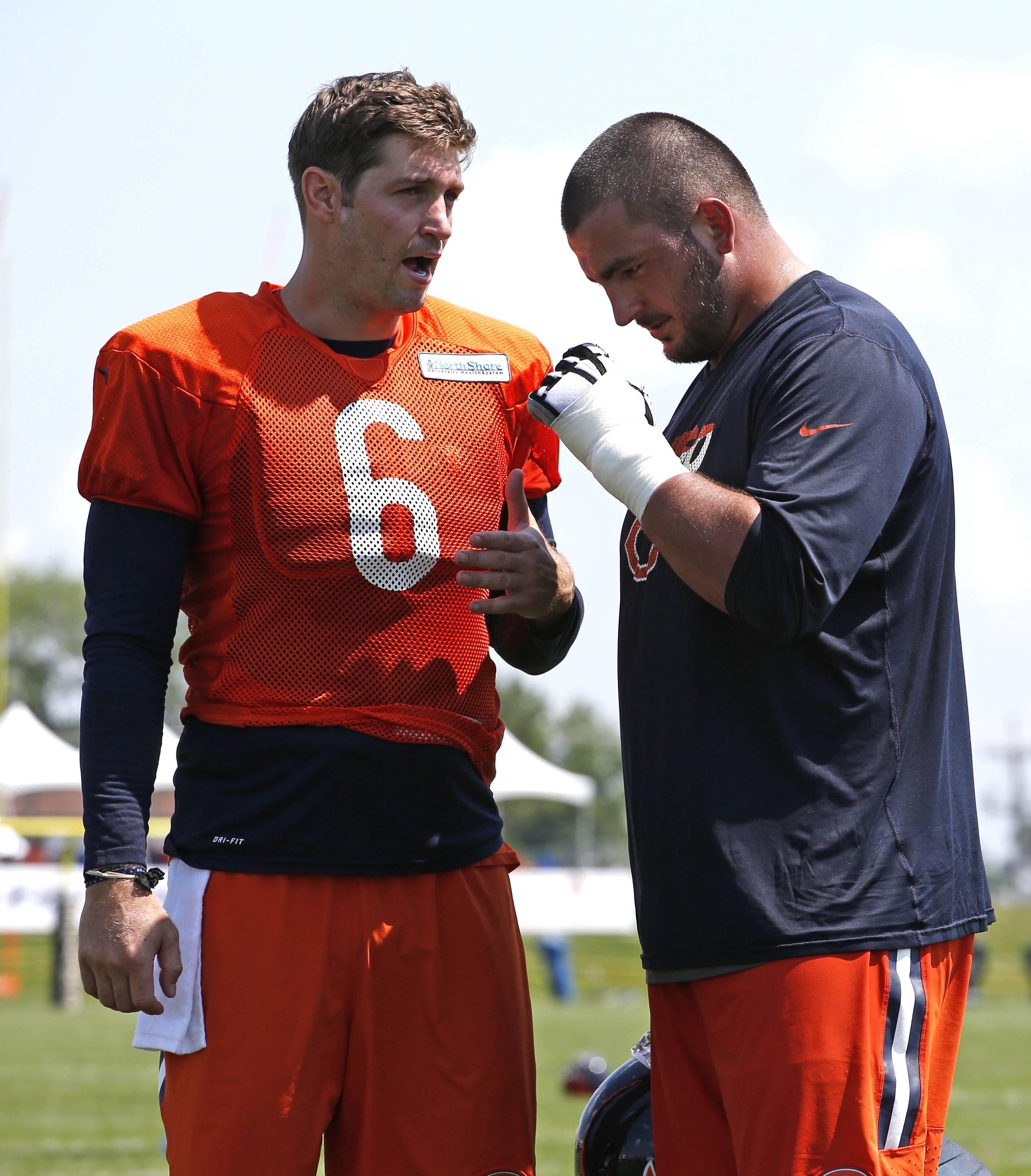 Bears quarterback Jay Cutler, left, talks with center Hroniss Grasu during practice at the NFL football teams training camp at Olivet Nazarene University, in Bourbonnais on Thursday. Thursday's strained calf that kept three-time Pro Bowl offensive lineman Kyle Long out of Friday's practice and in a protective walking boot sheds more of a spotlight on young offensive linemen like center Hroniss Grasu.