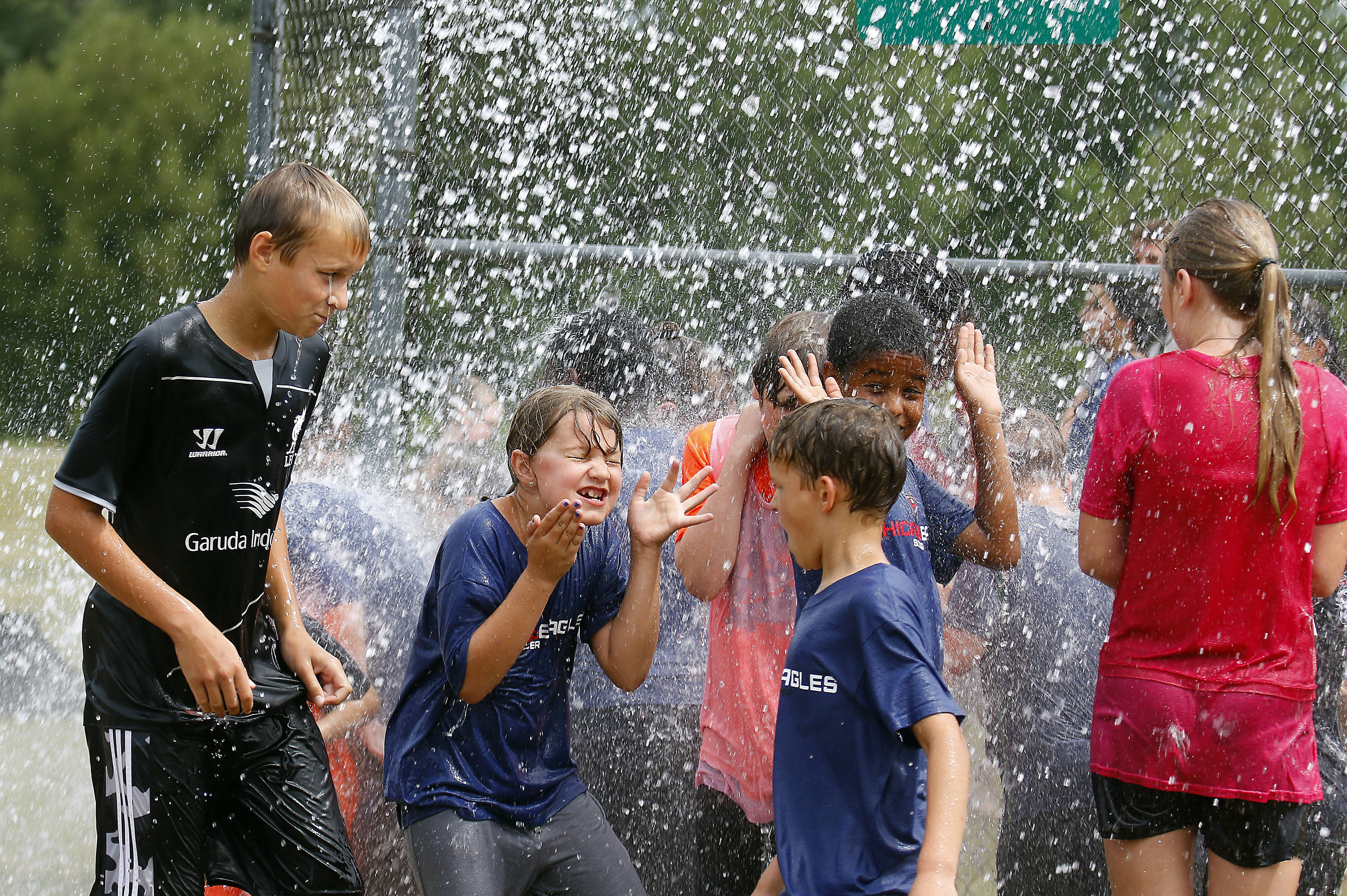 Kids at Chicago Eagles Soccer Camp at Dundee Middle School are sprayed by the Rutland-Dundee Township Fire Department, which came out to hose them down because of the heat.