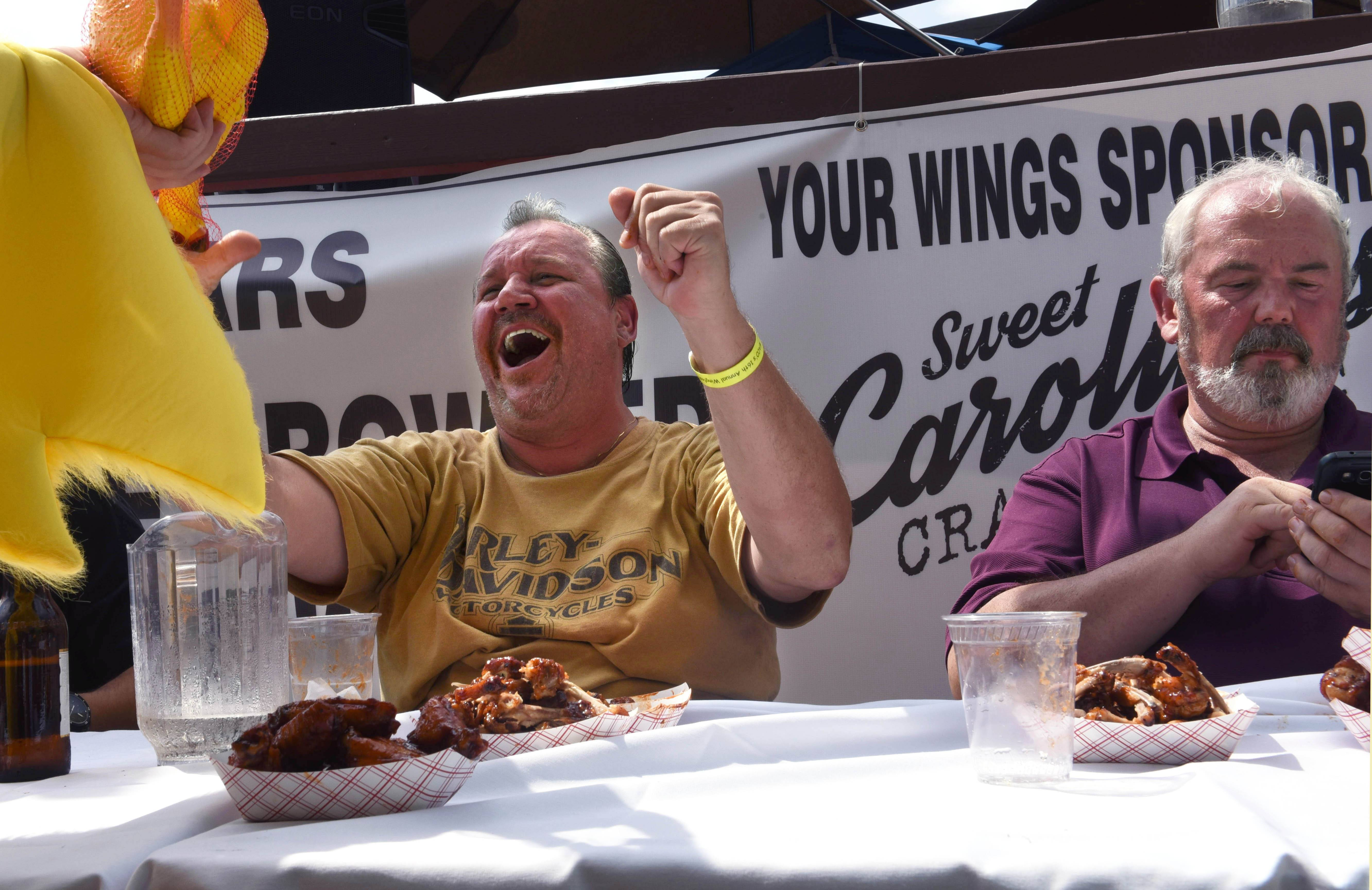 Joe Daniszewski of Mount Prospect celebrates after winning a wing-eating contest Sunday during the Woodfield Area Children's Organization's 16th annual Wingfest & Bags Tournament in Schaumburg.