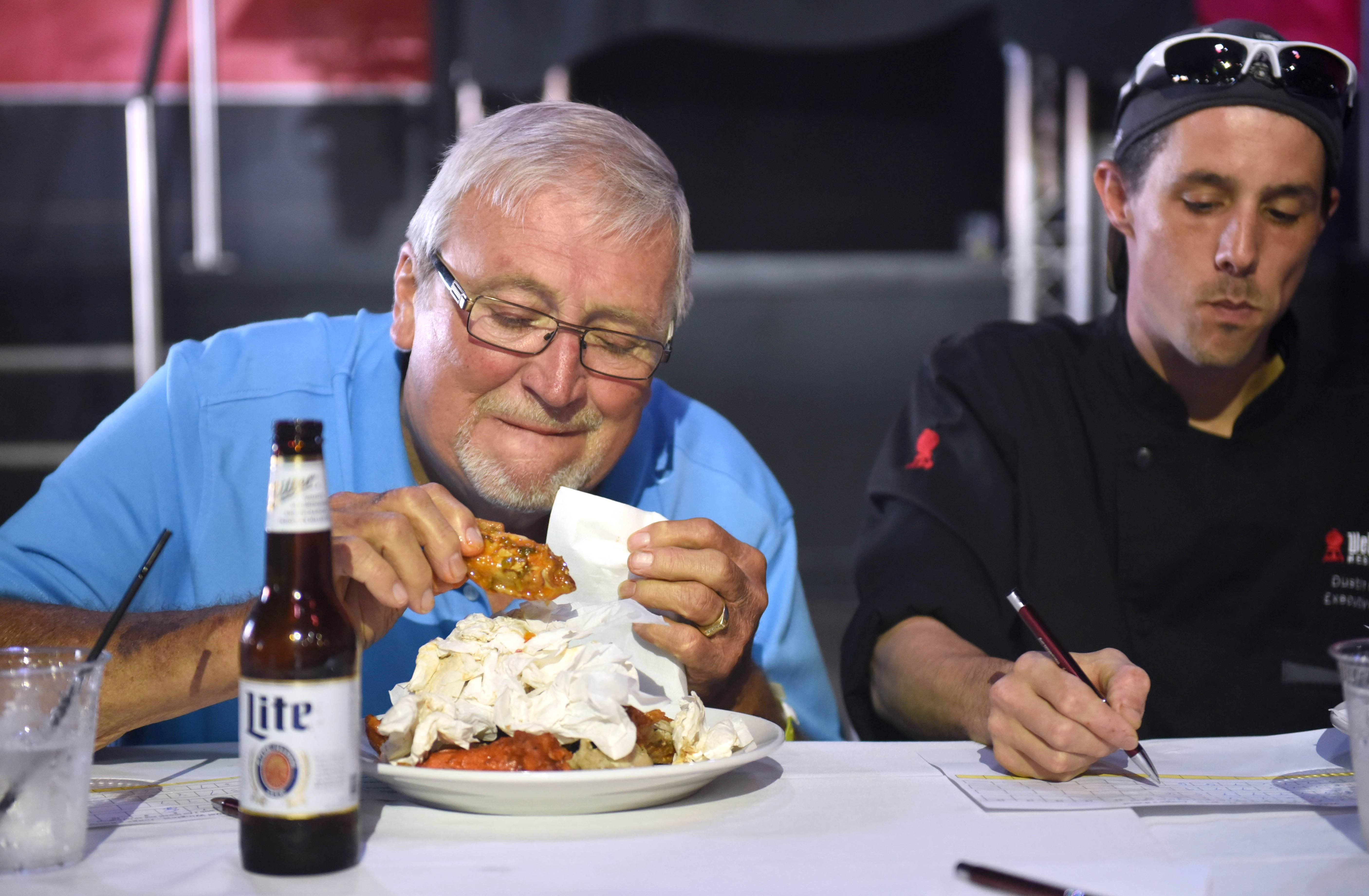 Schaumburg Trustee Frank Kozak, left, and Weber Grill Executive Chef Dustin Green judge wings Sunday during the Woodfield Area Children's Organization's 16th annual Wingfest & Bags Tournament in Schaumburg.