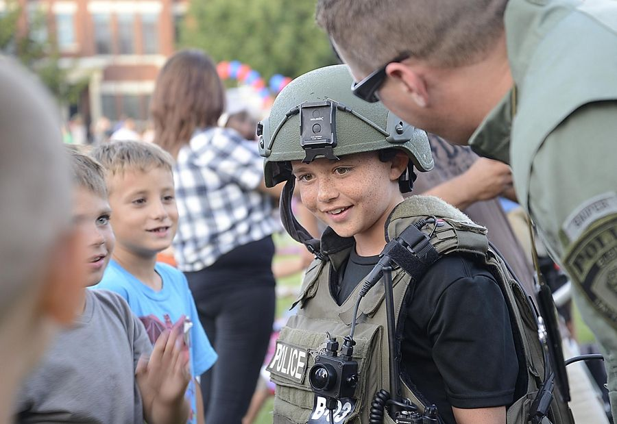 Daniel Pawlisch, 9, tries on Elgin SWAT gear as his brothers Avery, 6, and Matthew, 7, watch at the Elgin National Night Out event at Festival Park.