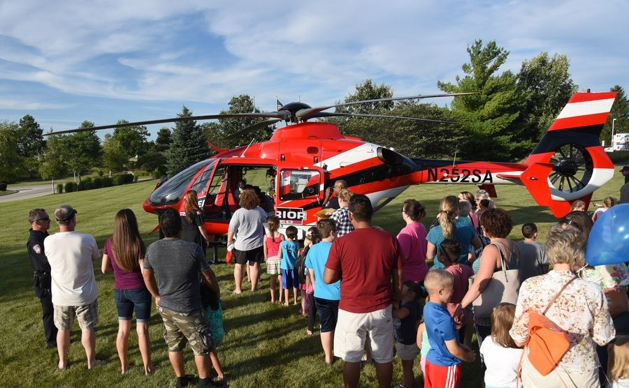 Families wait in line on the front lawn at the Kane County Judicial Center campus to see a Superior Air Ambulance up close at the Kane County Sheriff's National Night Out celebration in St. Charles.