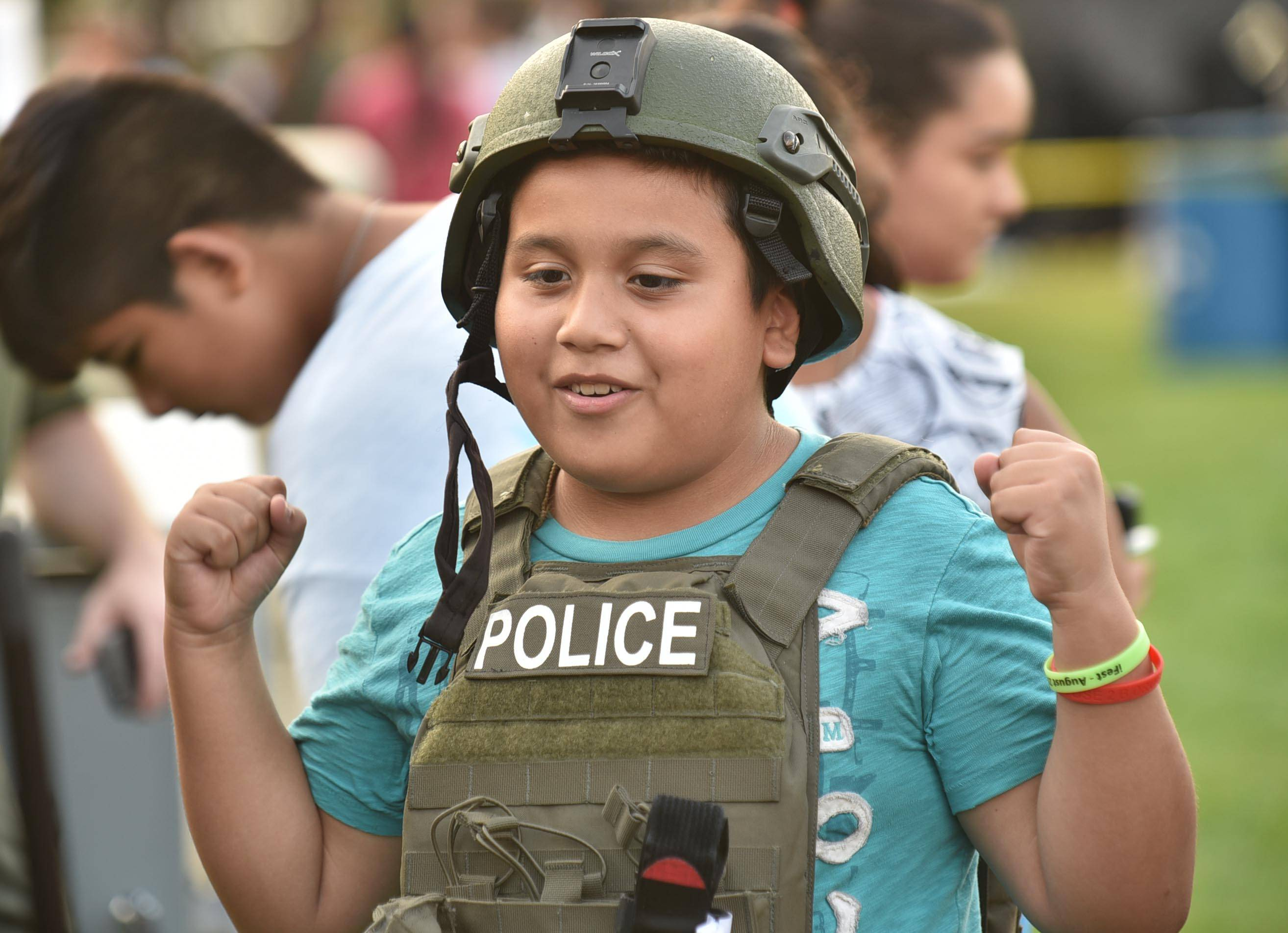 Dennis Martinez, 9, of Carpentersville pumps his fists while trying on police SWAT gear at Tuesday's National Night Out event at Festival Park in Elgin.