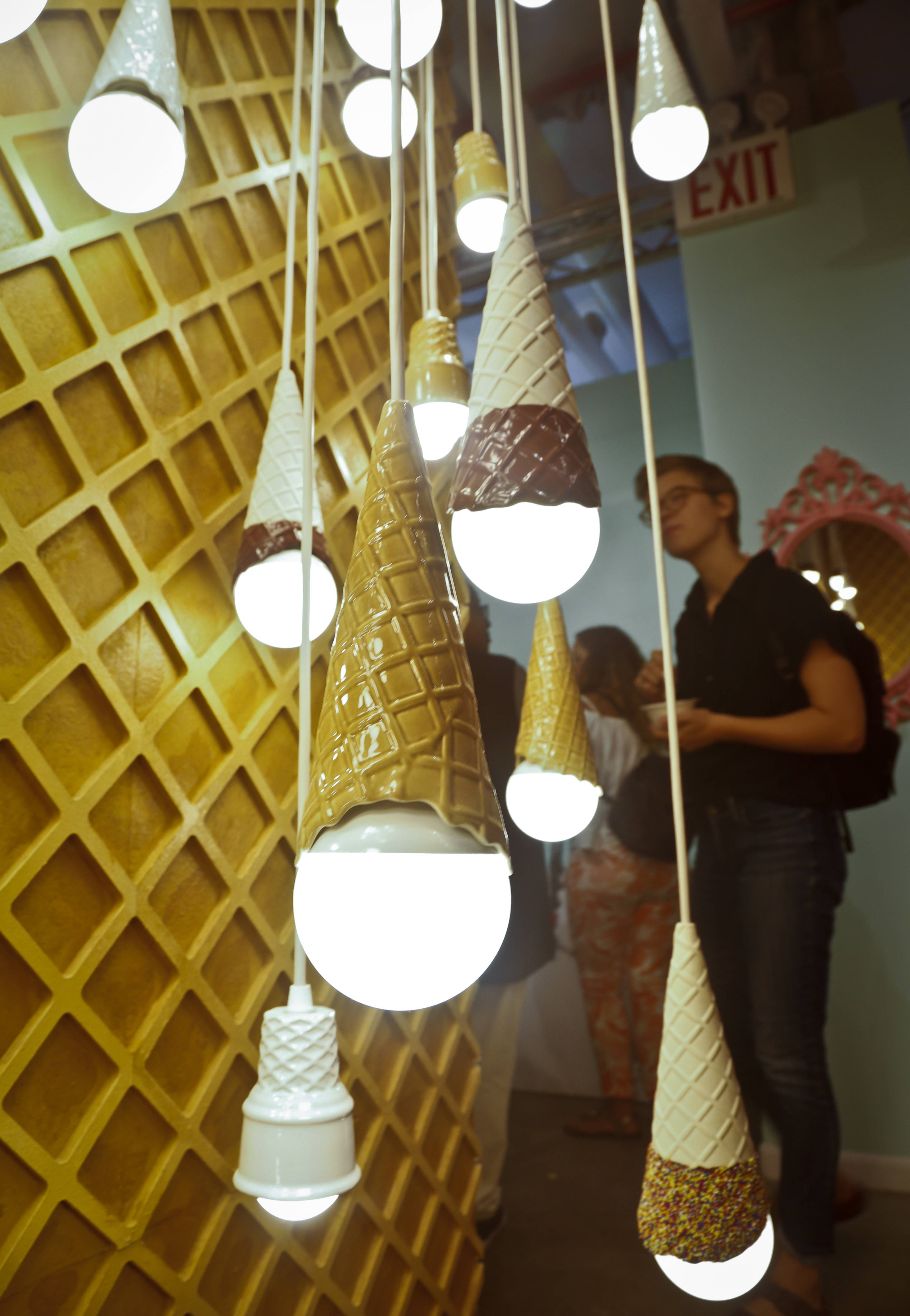 A waffle light wall featuring a series of hanging ice cream cones light bulbs is among ice cream-themed works of art at New York's Museum of Ice Cream.