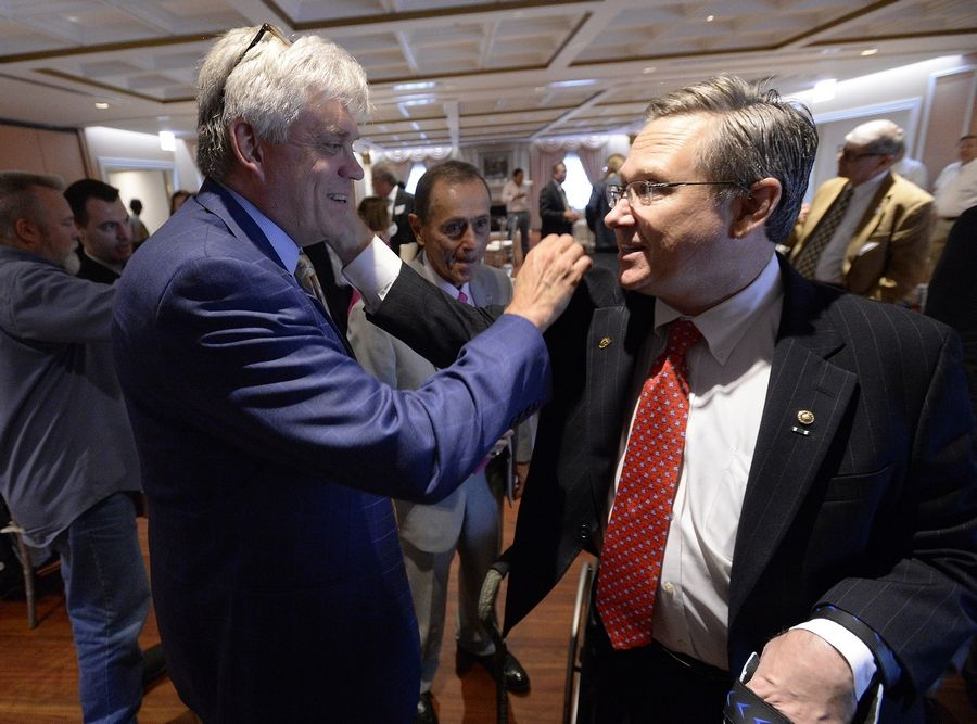 U.S. Sen. Mark Kirk greets businessman George Busse of Mount Prospect after Kirk discussed national security with members of suburban chambers of commerce in Arlington Heights.