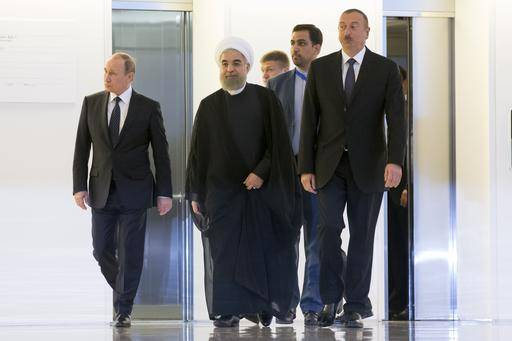 Russian President Vladimir Putin, left, Iranian President Hassan Rouhani, center, and Azerbaijan's President Ilham Aliyev, arrive to pose for a photo during their meeting in Baku, Azerbaijan, Monday, Aug. 8, 2016. Leaders of Azerbaijan, Iran, Russia are meeting to focus on boosting trade.