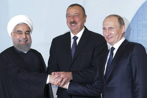 Iranian President Hassan Rouhani, left, Azerbaijan's President Ilham Aliyev, center, and Russian President Vladimir Putin pose for a photo during their meeting in Baku, Azerbaijan, Monday, Aug. 8, 2016. Leaders of Azerbaijan, Iran, Russia are meeting to focus on boosting trade.