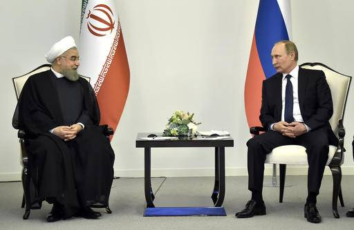 Russian President Vladimir Putin, right, meets with Iranian President Hassan Rouhani in Baku, Azerbaijan on Monday, Aug. 8, 2016. Leaders of Azerbaijan, Iran, Russia are meeting in Baku to focus on boosting trade. (Alexander Nemenov/Pool photo via AP)