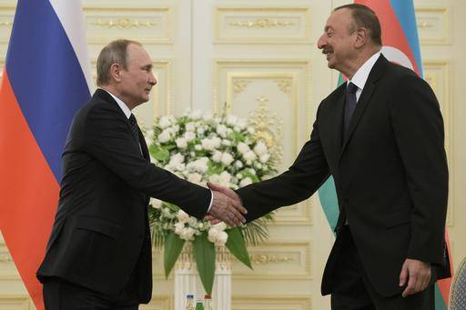 Russian President Vladimir Putin, and Azerbaijan's President Ilham Aliyev greet each other during their meeting in Baku, Azerbaijan, Monday, Aug. 8, 2016. Leaders of Azerbaijan, Iran, Russia are meeting to focus on boosting trade.