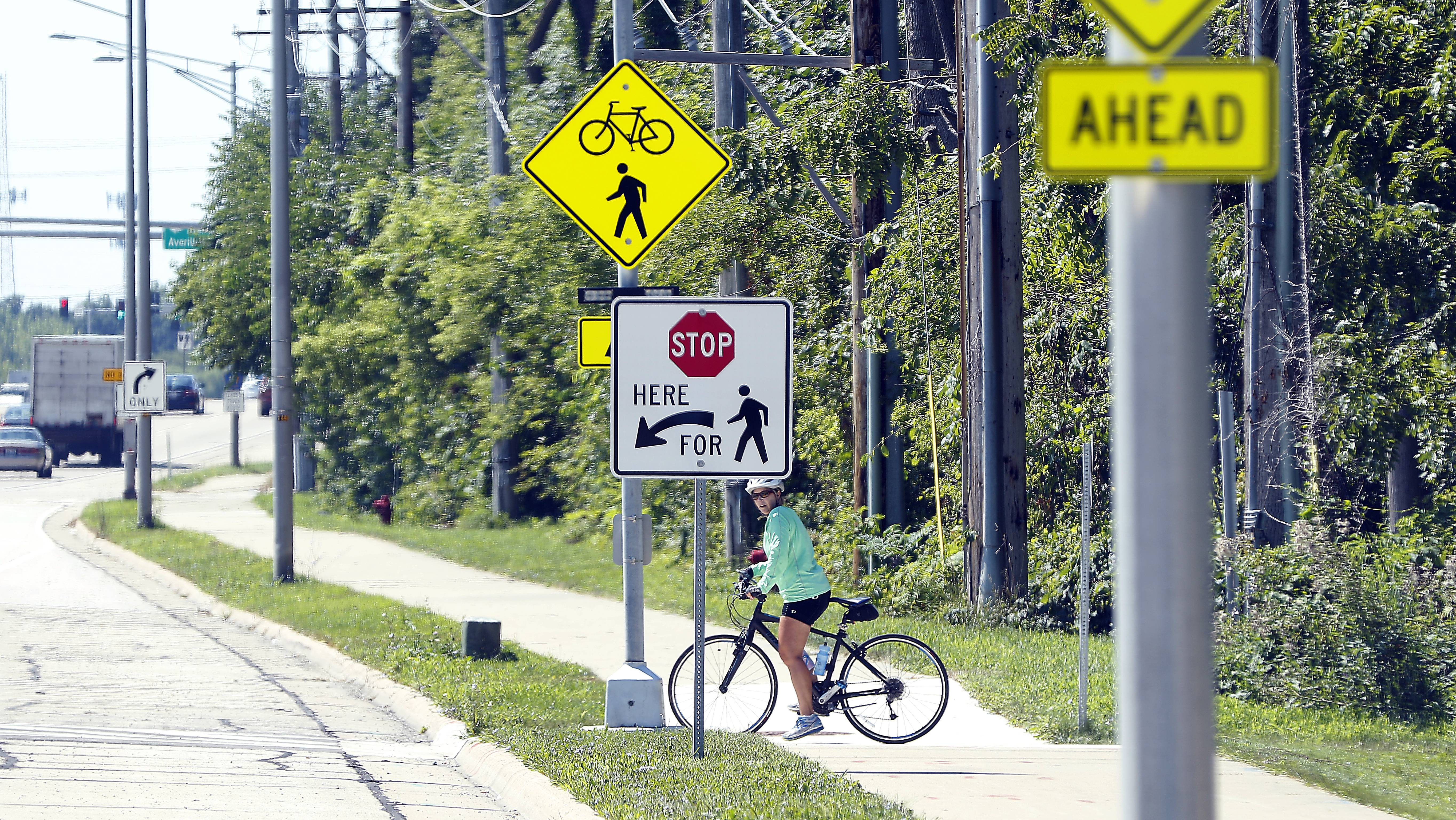 A cyclist pauses at a pedestrian-activated flashing crosswalk light at Kirk Road and the Prairie Path in Geneva. A similar signal has created controversy in Mount Prospect after a cyclist died when a driver failed to yield in June.