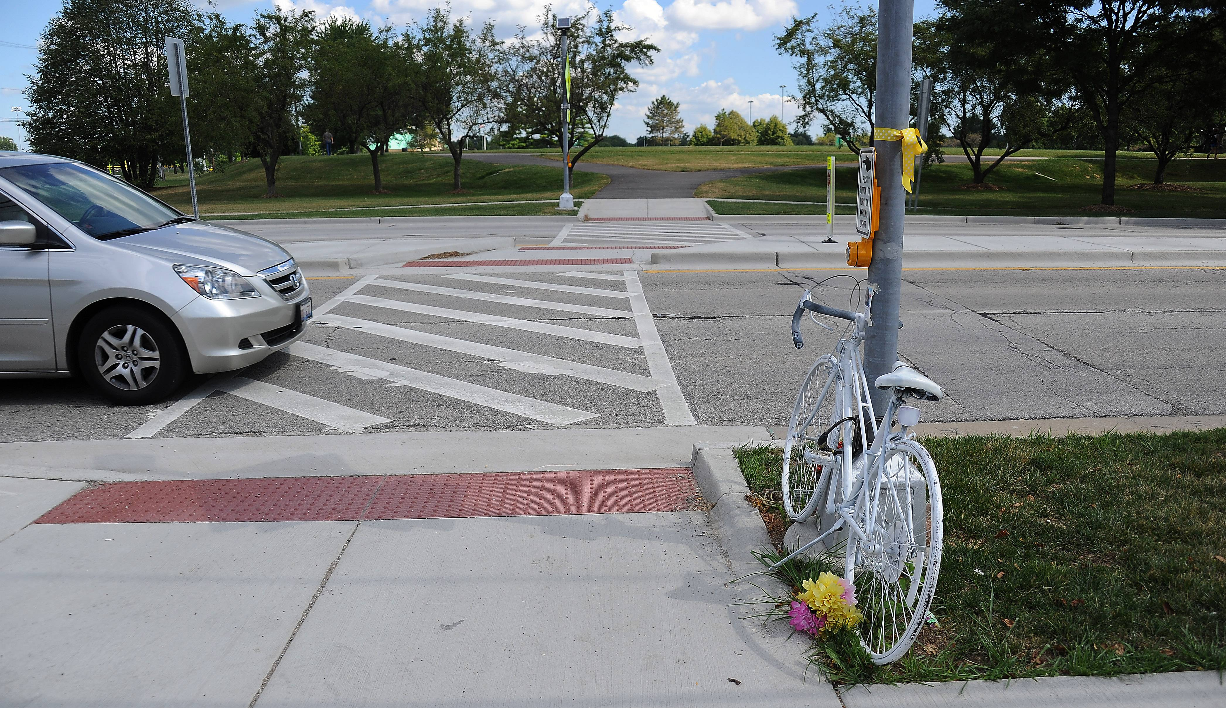 "A memorial ""Ghost Bike"" now sits at the crosswalk in Mount Prospect where cyclist Joni Beaudry was killed June 9 by an SUV. Residents are concerned the flashing light signal intended to protect pedestrians isn't effective."