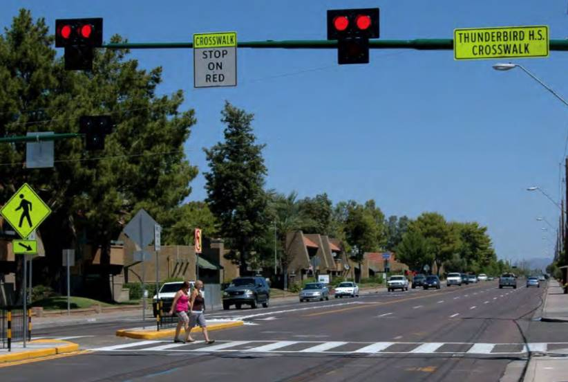 A pedestrian hybrid beacon uses yellow warning lights, then a red light to warn drivers to stop for pedestrians in crosswalks.
