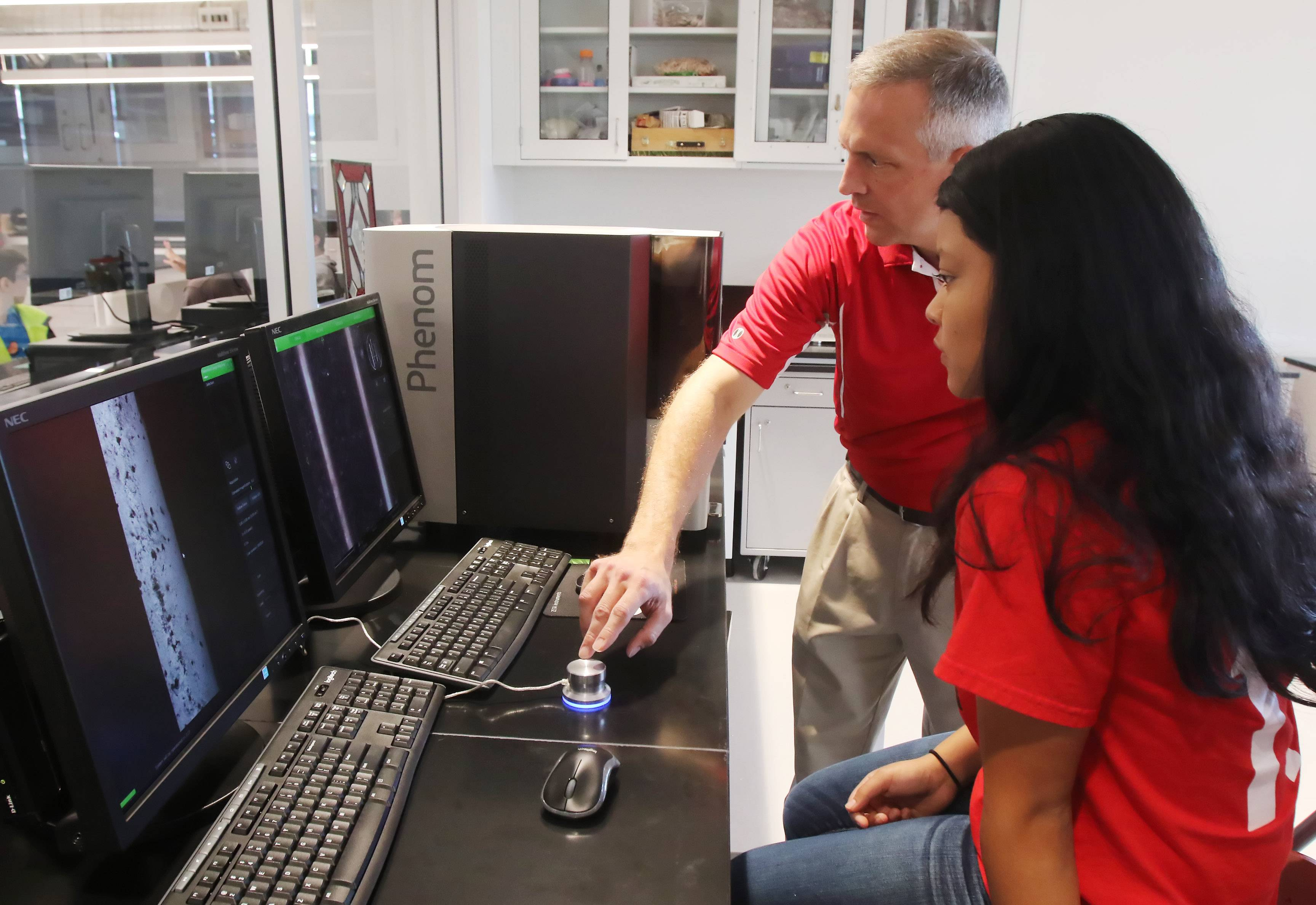 Science Department leader David Greenwood shows senior Jisel Gomez how to use a new scanning electron telescope Tuesday at Mundelein High School. The device can be found in a newly completed wing dedicated to science, technology, engineering and math education.