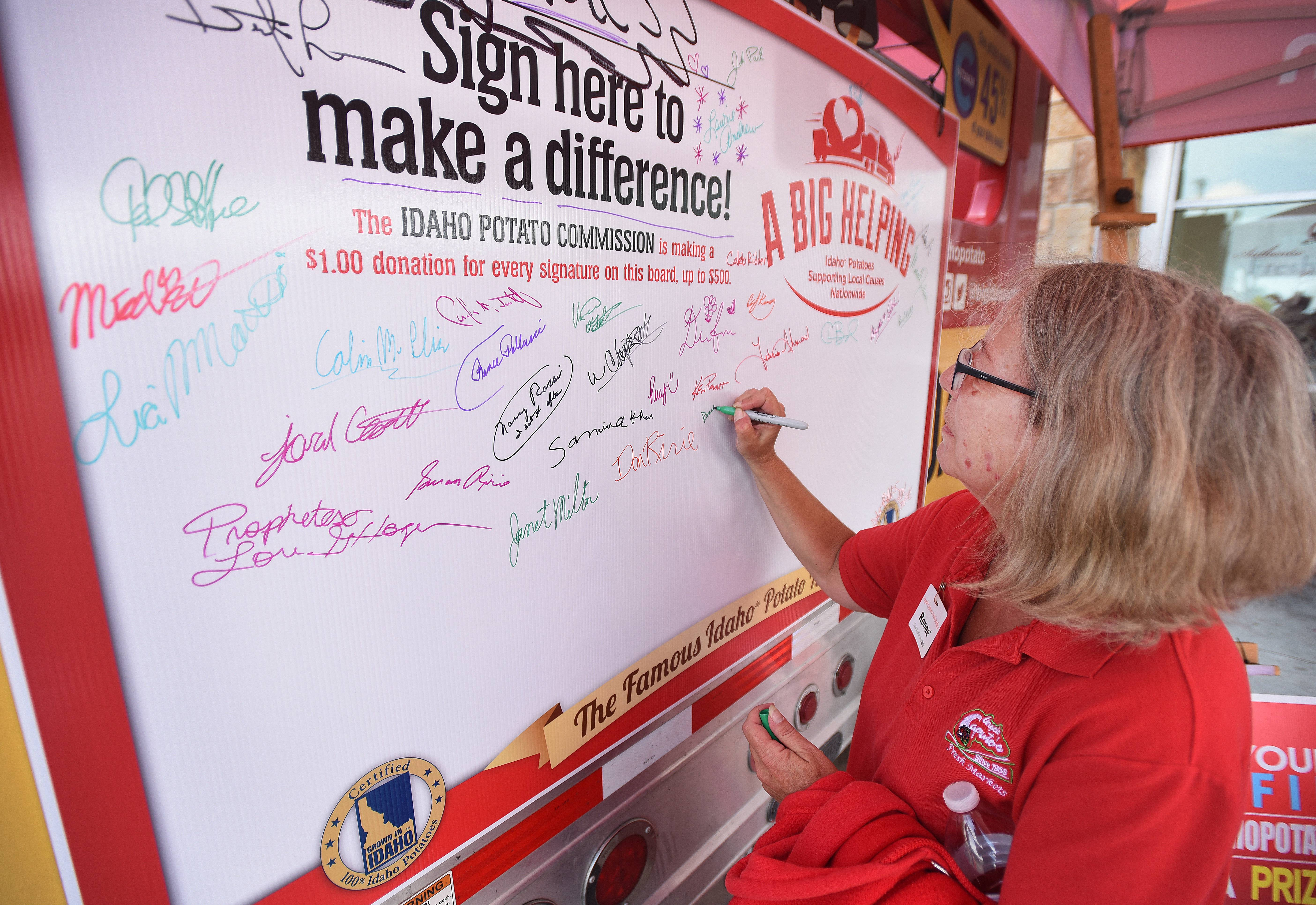 Renee Kostel of West Chicago signs on near the potato truck. For every signature, the Idaho Potato Commission pledged to donate a $1 to the St. Jude Children's Research Hospital.