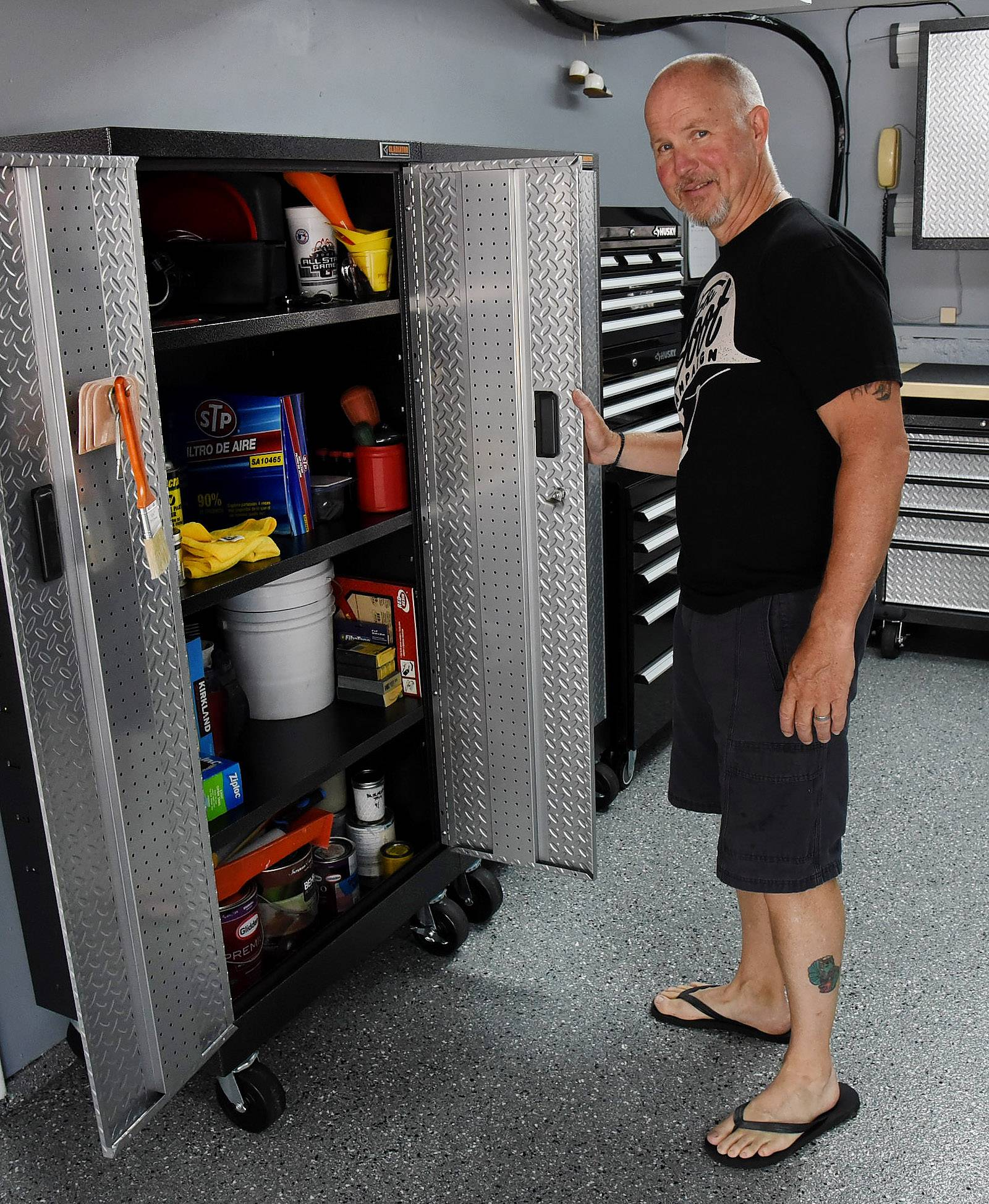 Rob Ruisz shows off a new cabinet in the garage where he entertains and works on vehicles.