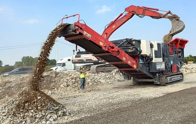 "A mobile crusher known as the ""mother ship"" grinds up old concrete from the Jane Addams Tollway (I-90). It's then reused to build a new road."