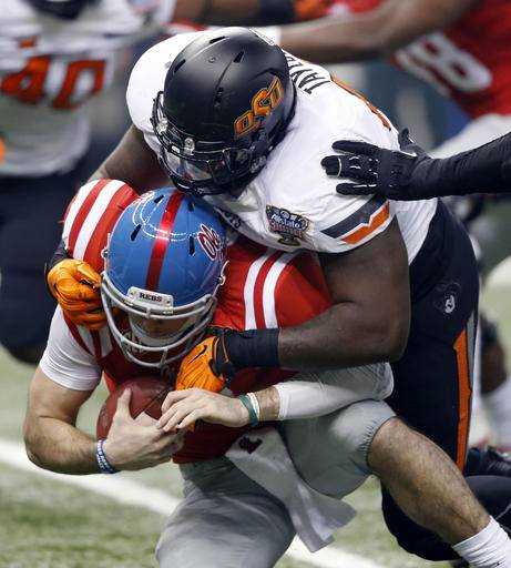 FILE - In this Jan. 1, 2016, file photo, Mississippi quarterback Chad Kelly (10) is brought down by Oklahoma State defensive tackle Vincent Taylor (96) in the first half of the Sugar Bowl college football game in New Orleans. Defensive line coach Joe Bob Clements is looking forward to big things from tackle Vincent Taylor, a junior who compiled five sacks and 48 tackles last season (AP Photo/Bill Feig, File)