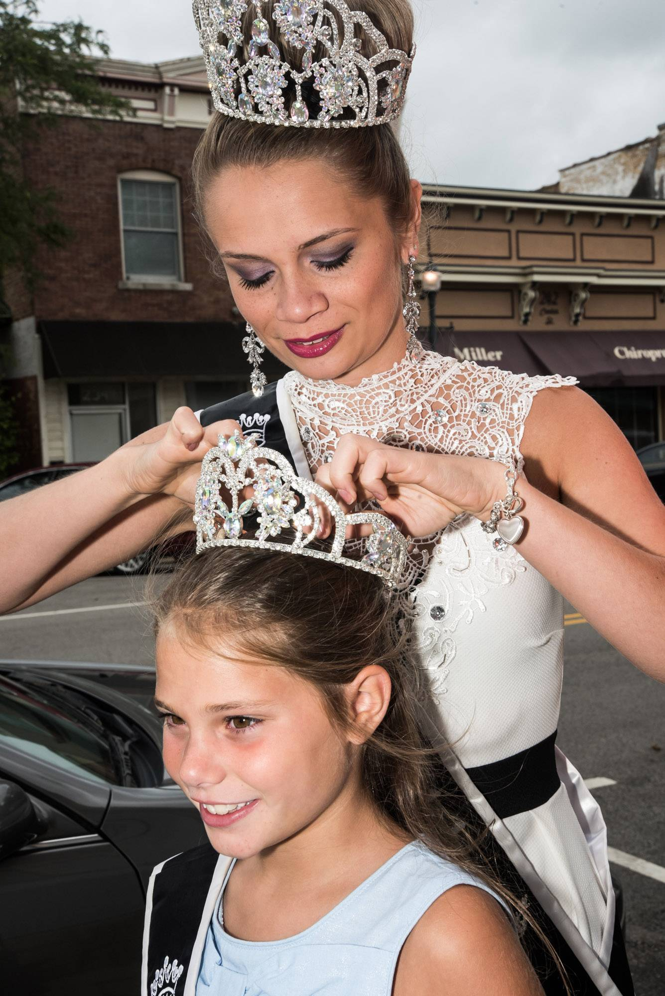 Miss Grayslake Jessi Bryson, 20, gives Little Miss Grayslake Sarah Bianchi, 9, some last-minute tiara help ahead of Summer Days festivities Saturday.