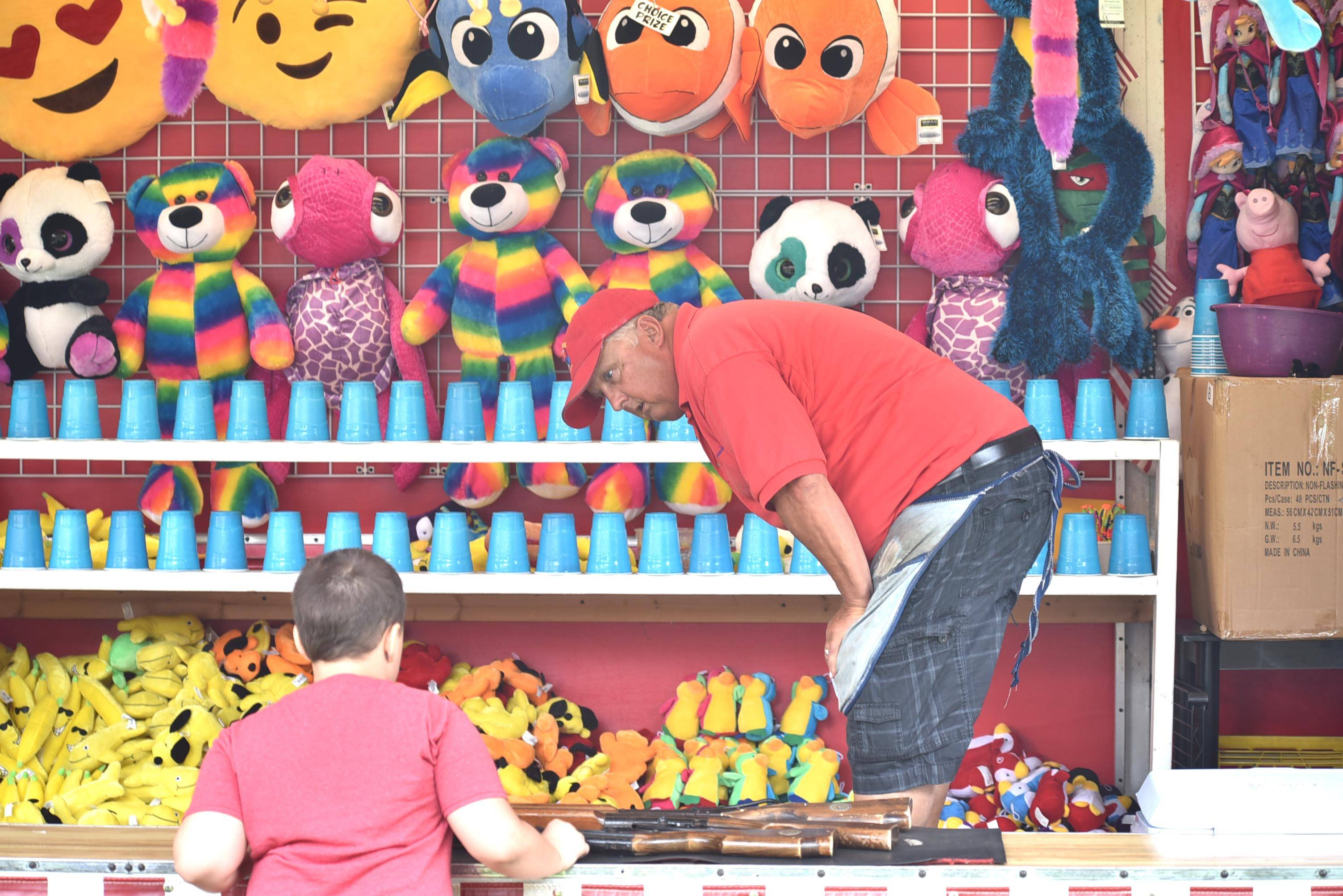 Paul Kasin helps a winner pick out his prize in a midway game Saturday at the Elburn Days festival in Lions Park. Kasin's Grayslake family owns and operates games that appear at most of the local festivals.
