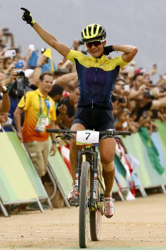 Jenny Rissveds of Sweden celebrates as she crosses the finish line to win the women's cross-country mountain bike race at the 2016 Summer Olympics in Rio de Janeiro, Brazil, Saturday, Aug. 20, 2016. (AP Photo/Patrick Semansky)