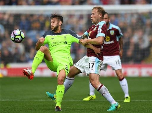 Liverpool's Adam Lallana, left, and Burnley's Scott Arfield in action during their English Premier League soccer match at Turf Moor, Burnley, England, Saturday Aug. 20, 2016. (Anthony Devlin / PA via AP)