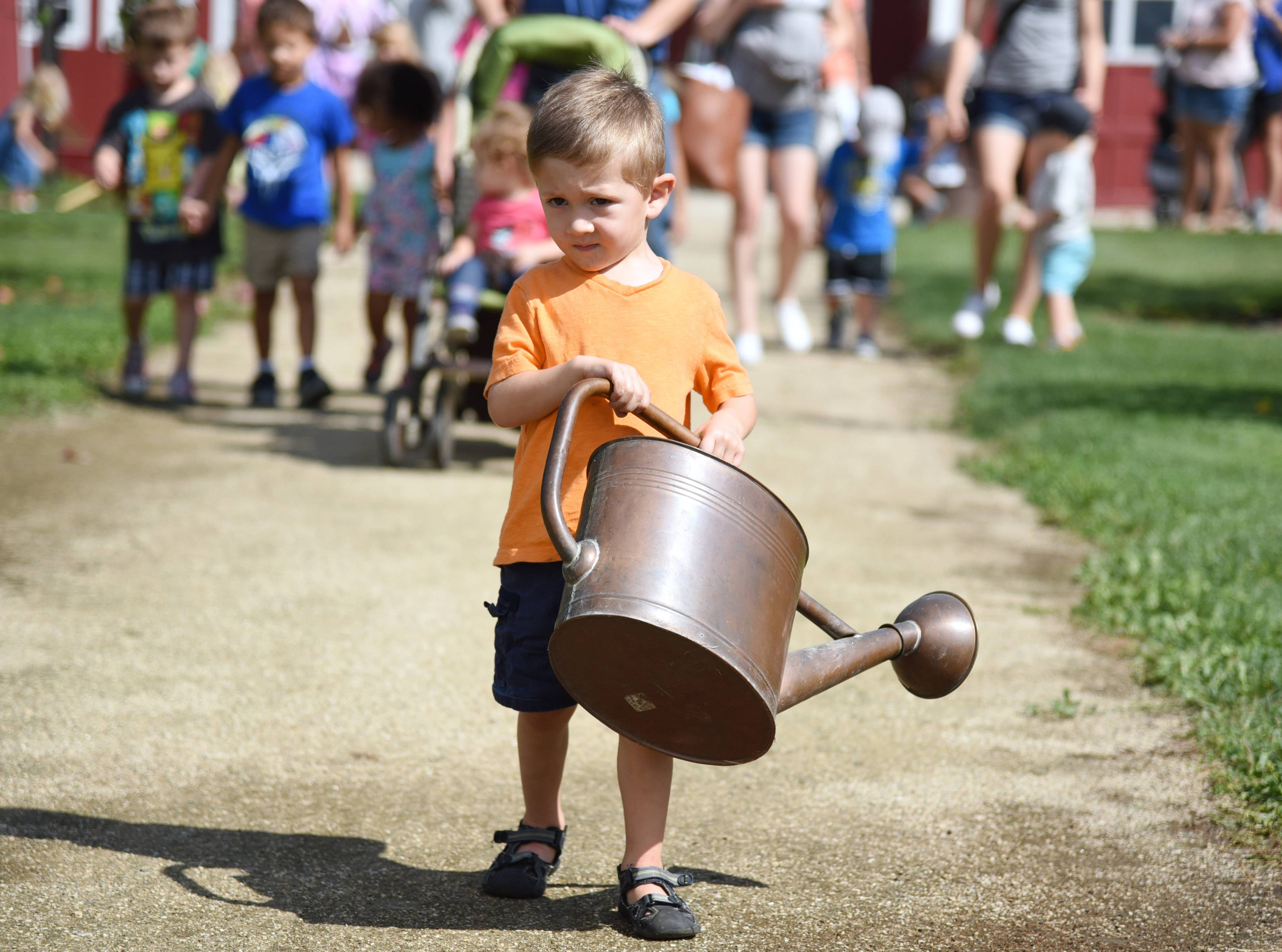 Two-year-old Joey Canino, of Grayslake heads to the Bonner Heritage Farm garden Wednesday during the Lake County Forest Preserve District Little Sprouts program called Fresh from the Garden.